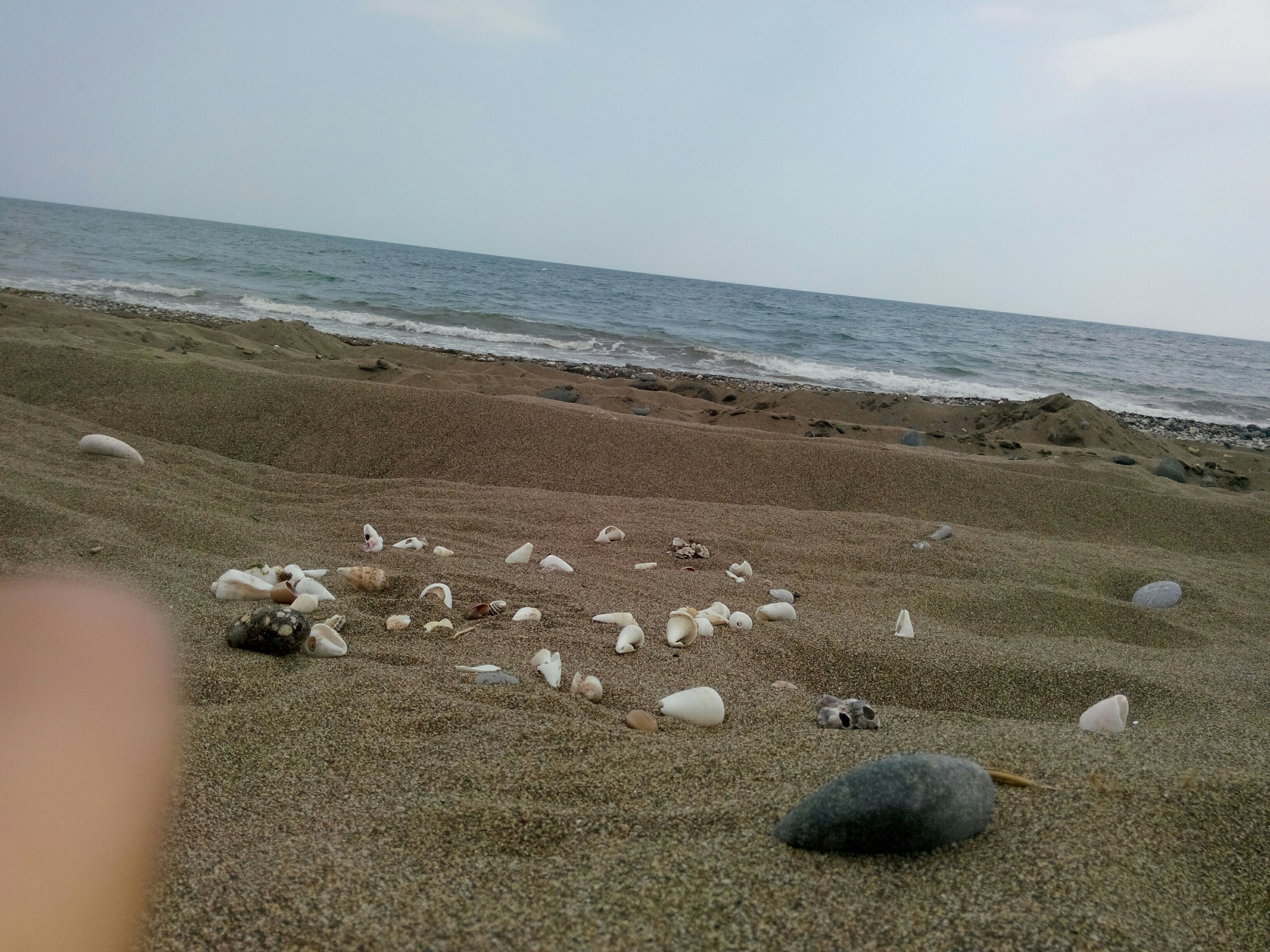 beach, sea, sand, horizon over water, shore, water, sky, tranquility, tranquil scene, scenics, nature, beauty in nature, coastline, pebble, day, stone - object, outdoors, idyllic, vacations, remote