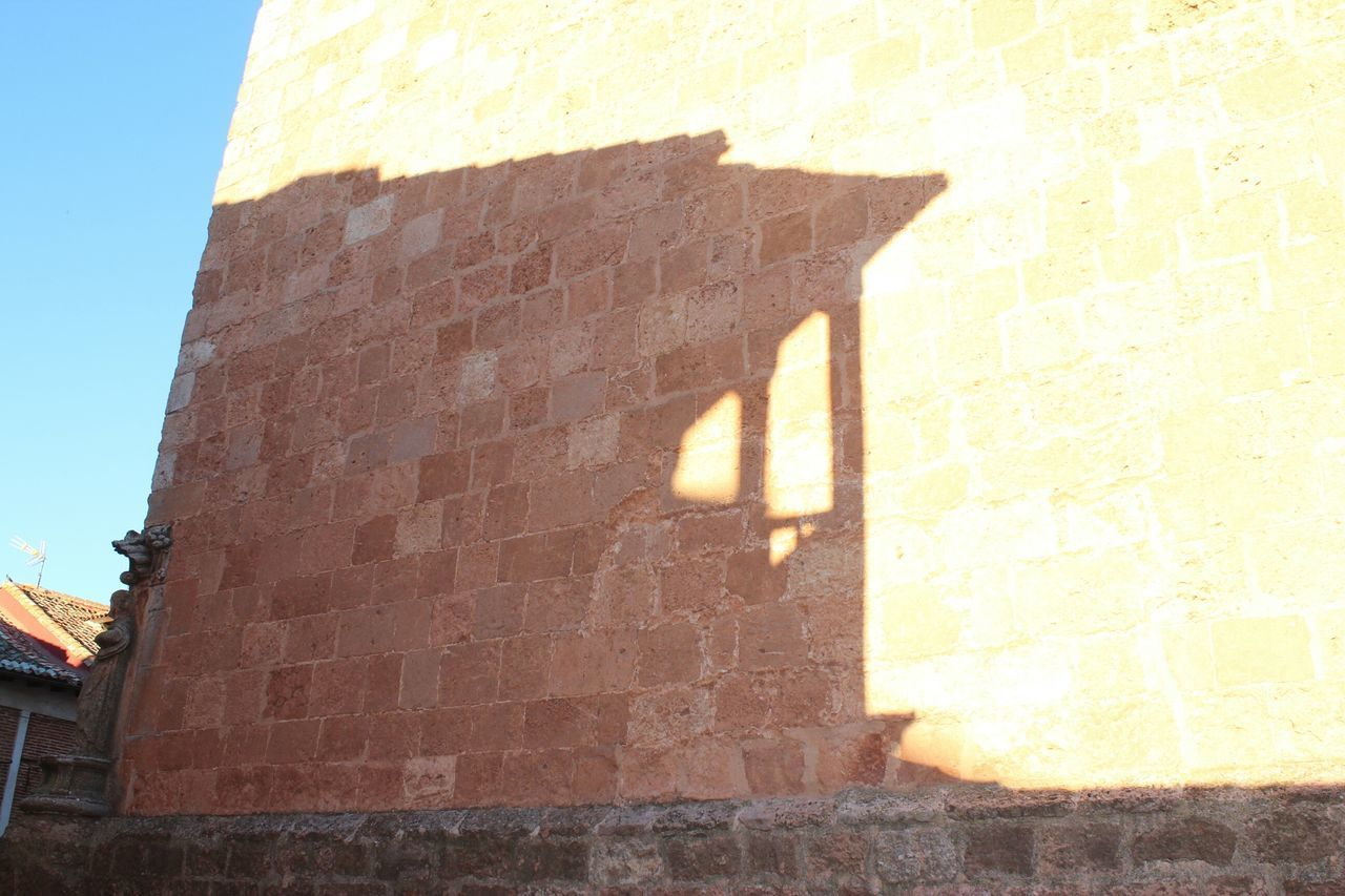 sunlight, shadow, architecture, built structure, day, brick wall, building exterior, outdoors, low angle view, sunny, no people, sky