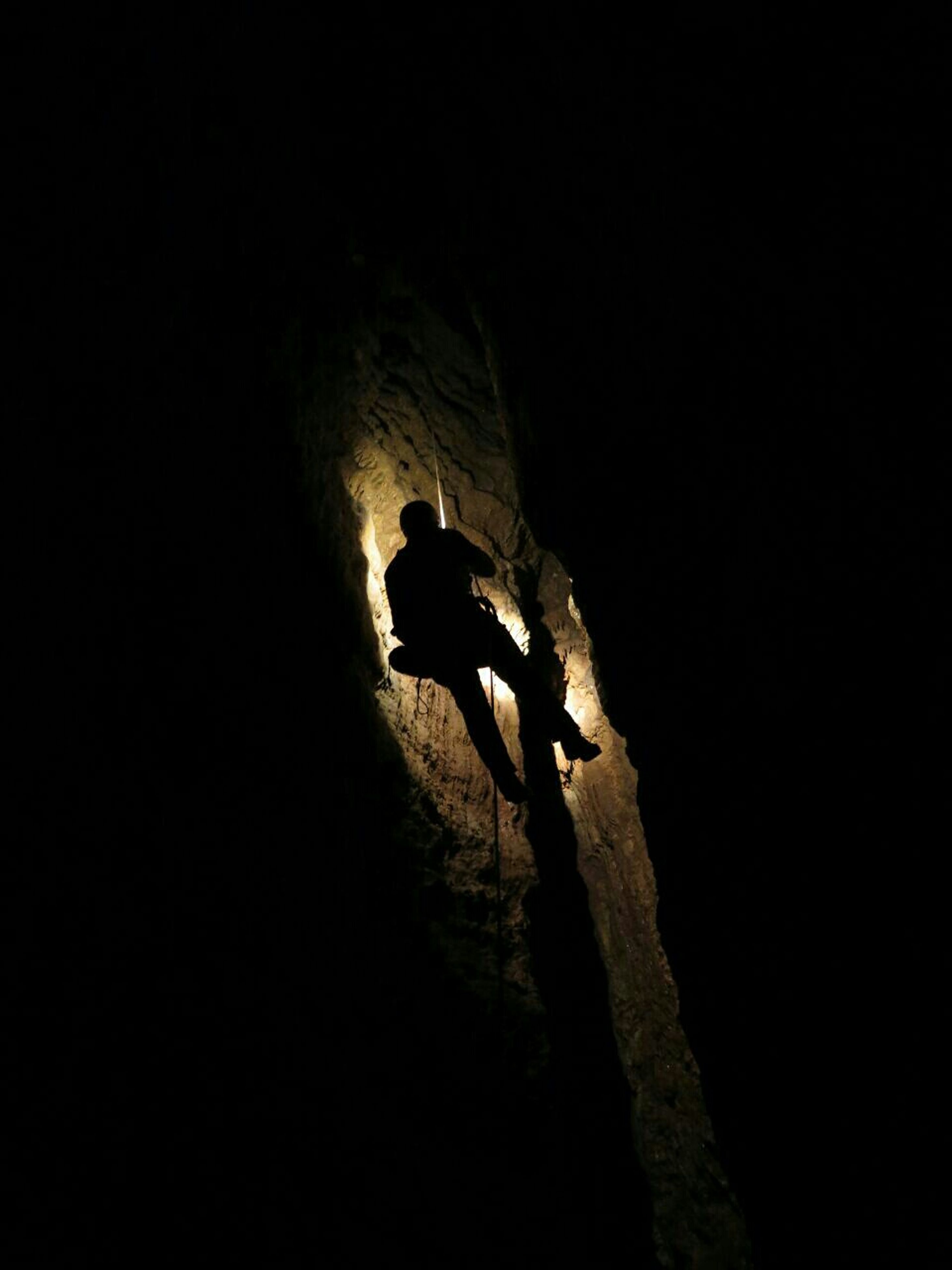 silhouette, lifestyles, men, leisure activity, full length, unrecognizable person, adventure, extreme sports, high angle view, rock - object, standing, low angle view, exploration, copy space, outdoors, night, person
