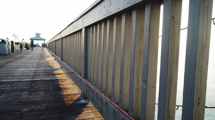 Seeing From A Child's Perspective The Way Forward Shadows Sunlight Slats Fishing Pier From My Point Of View Pier Over Water Boardwalk Wood - Material Outdoors Day Wood - Material Built Structure Adult People Adults Only Sky Corrugated Iron