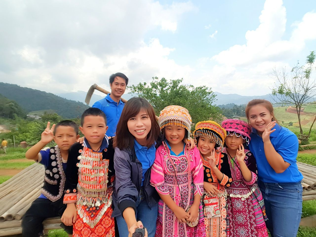 real people, medium group of people, looking at camera, togetherness, leisure activity, girls, day, sky, portrait, outdoors, boys, smiling, lifestyles, happiness, standing, tree, childhood, casual clothing, young women, elementary age, young adult, friendship, nature