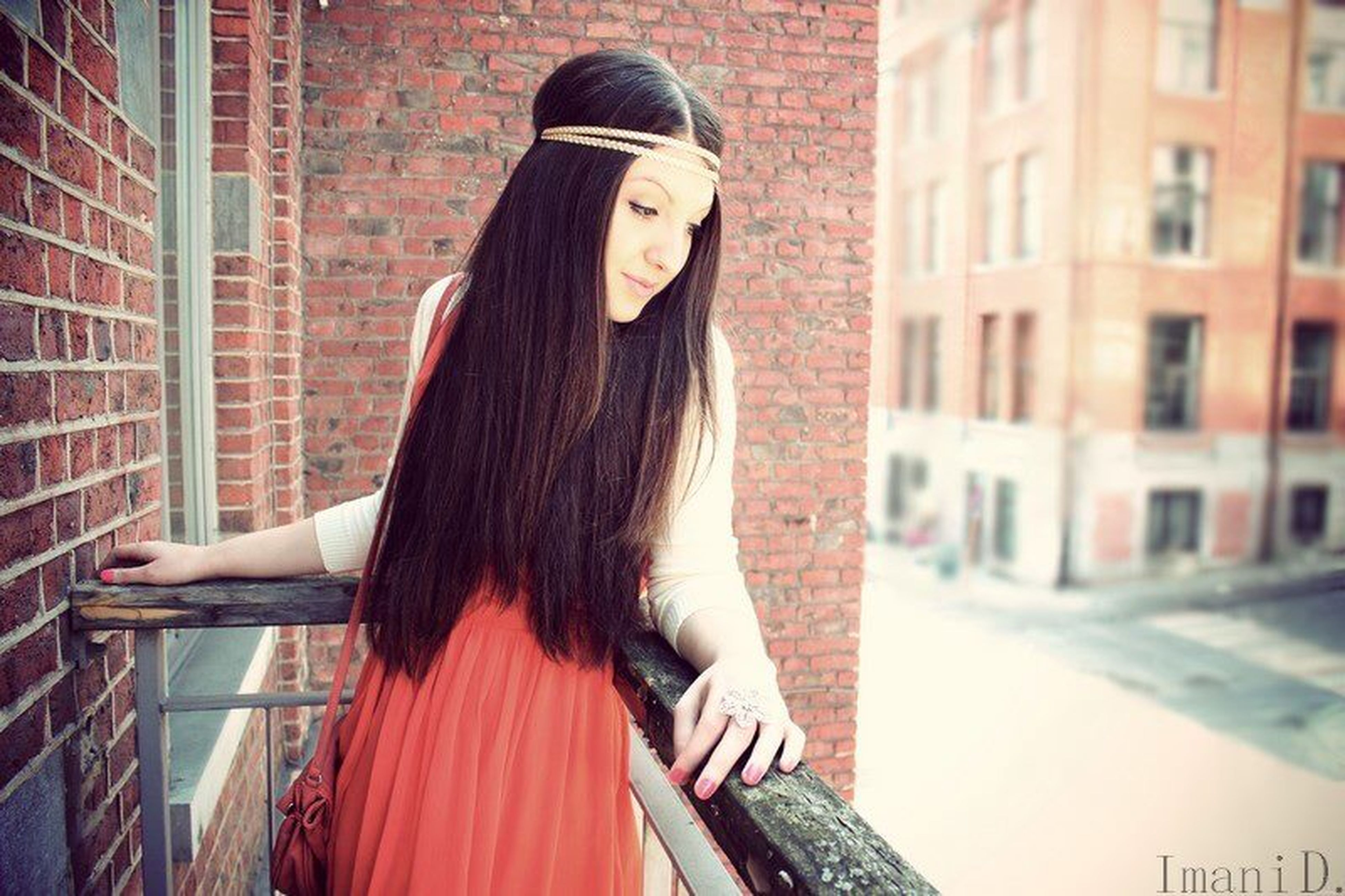 young adult, young women, building exterior, lifestyles, long hair, architecture, built structure, casual clothing, leisure activity, standing, three quarter length, side view, front view, person, brick wall, fashion