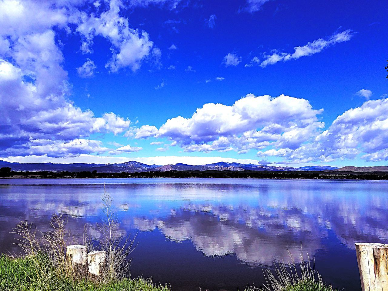 sky, scenics, reflection, tranquil scene, beauty in nature, tranquility, nature, cloud - sky, water, lake, no people, blue, outdoors, day, landscape, mountain, grass