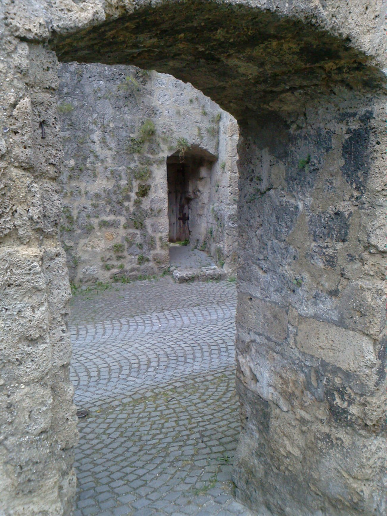 ... View from an archway to a small door at an exremely old castle in Tittmoning, Bavaria, Germany