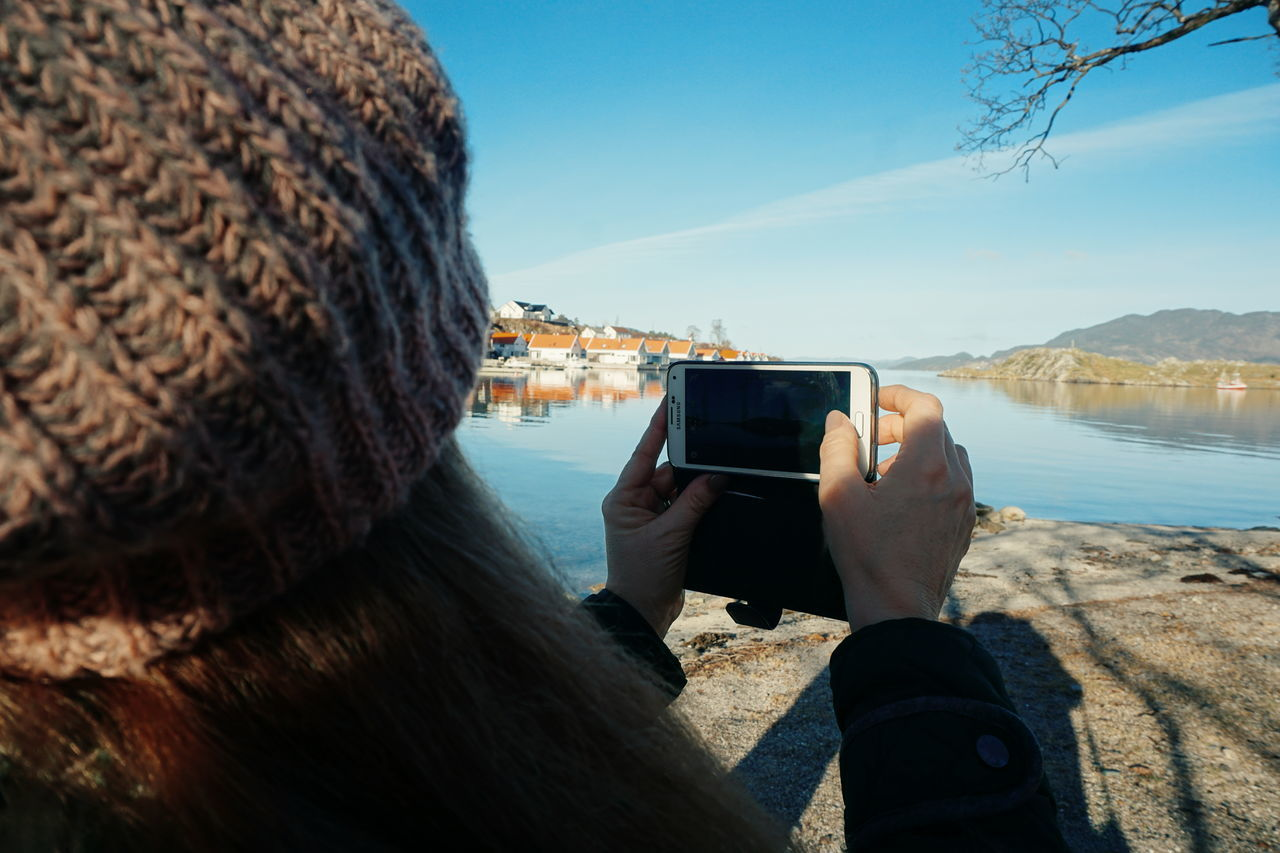 taking photos Photography Themes Wireless Technology Photographing Portable Information Device Smart Phone Mobile Phone Photo Messaging Communication Selfie Technology Adults Only One Man Only Reflection Only Men Holding Travel Rear View Camera - Photographic Equipment Adult One Person Knitted Hat Winter Part Of Body Winter Clothes Unrecognizable Person