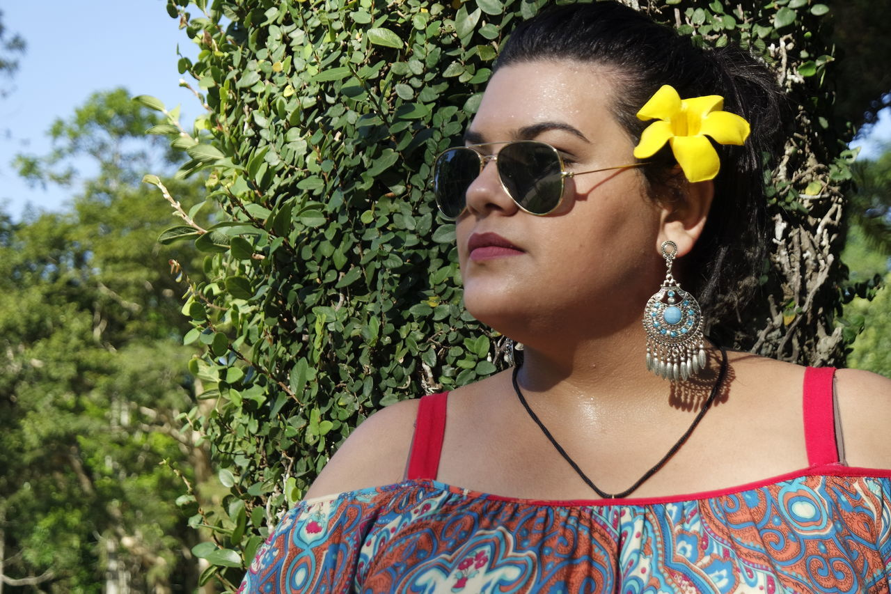 sunglasses, real people, outdoors, one person, day, tree, leisure activity, young adult, fashion, front view, headshot, focus on foreground, young women, lifestyles, beautiful woman, portrait, close-up, flower, nature
