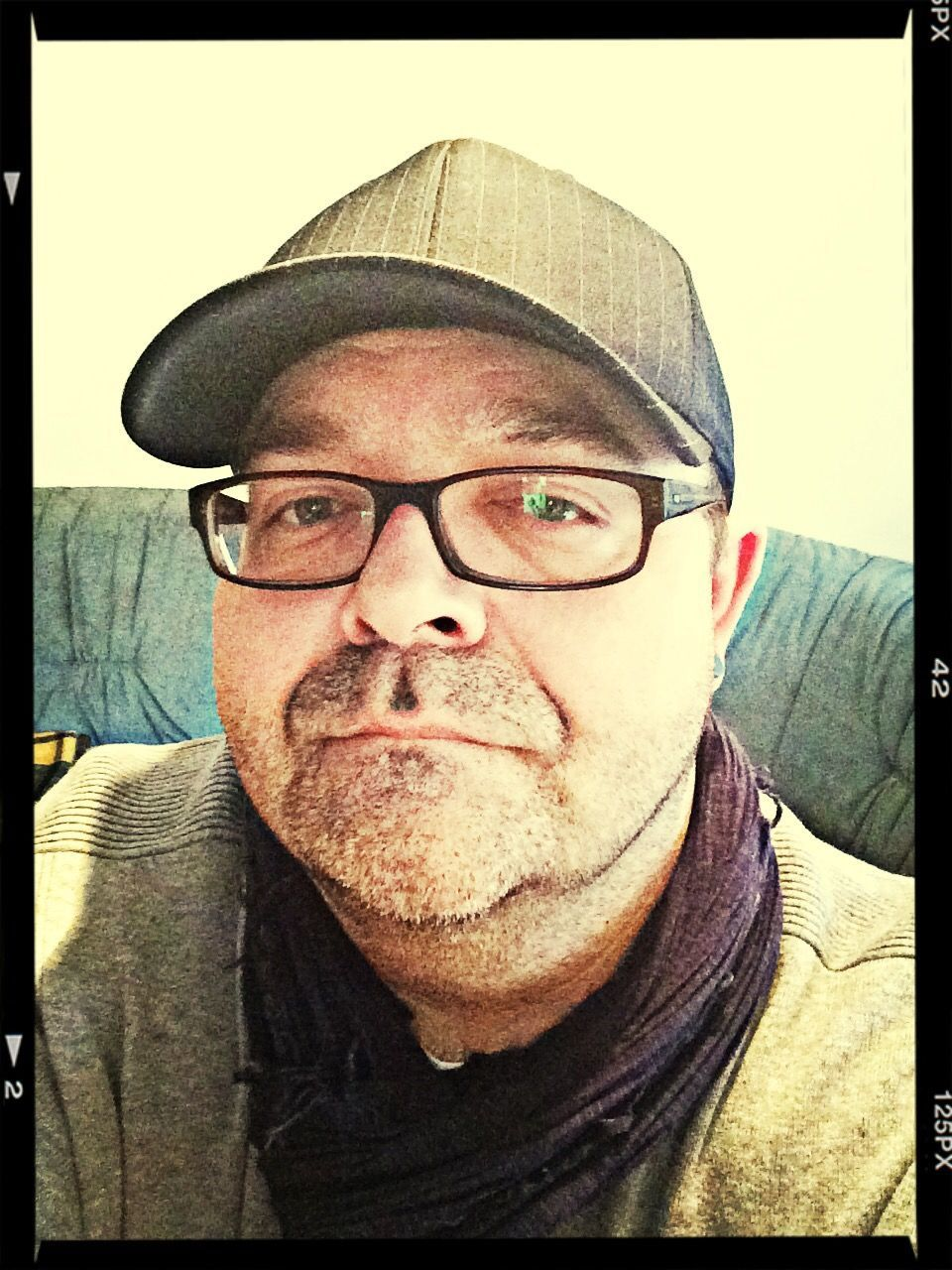 looking at camera, portrait, eyeglasses, front view, head and shoulders, glasses, one person, real people, headshot, mature men, cap, flat cap, lifestyles, mature adult, close-up, human face, day, young adult, indoors