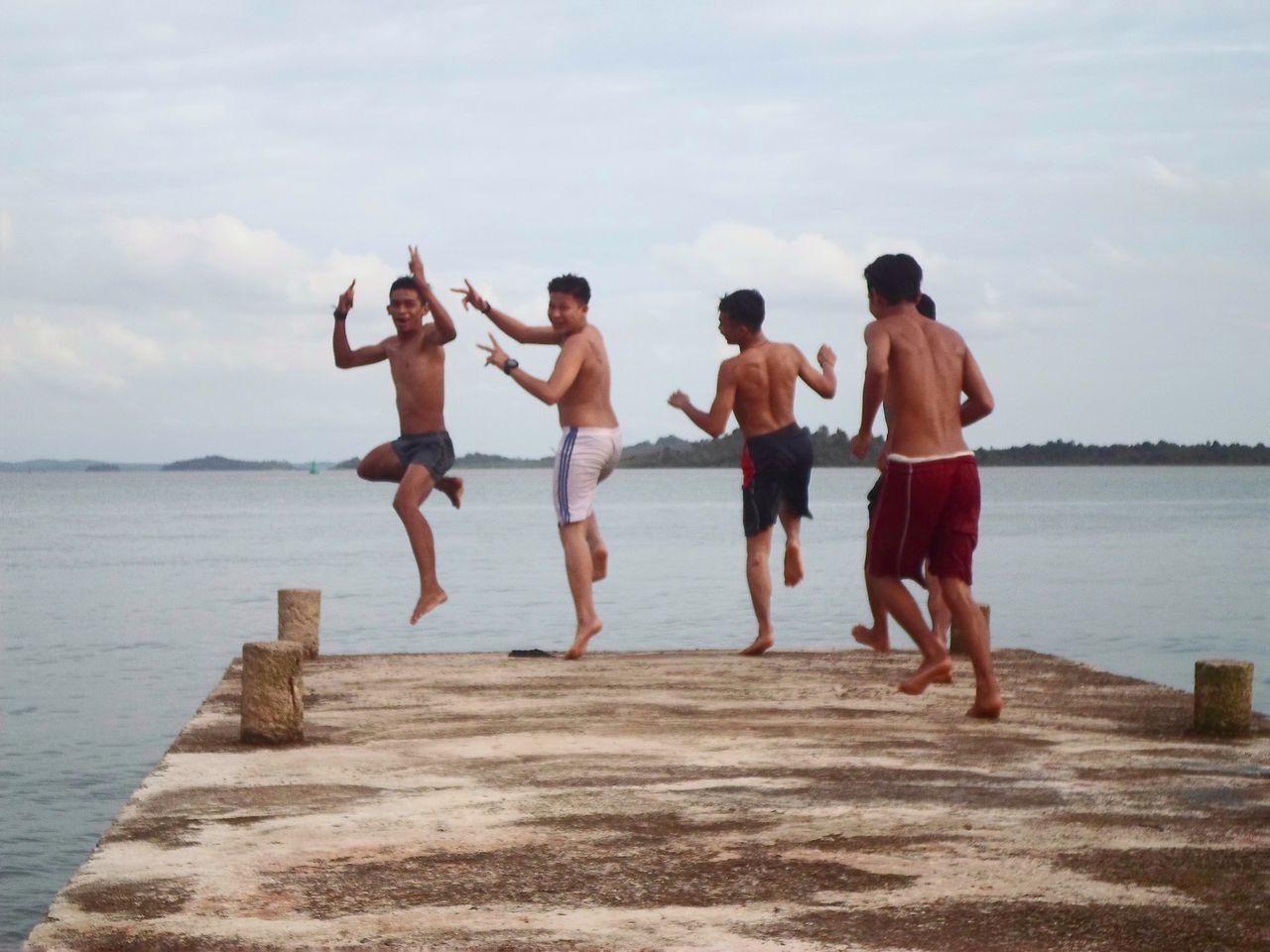 shirtless, water, sea, mid-air, full length, real people, jumping, leisure activity, outdoors, fun, vacations, day, togetherness, rear view, sky, enjoyment, lifestyles, men, motion, beach, nature, standing, friendship, young adult, adult, people