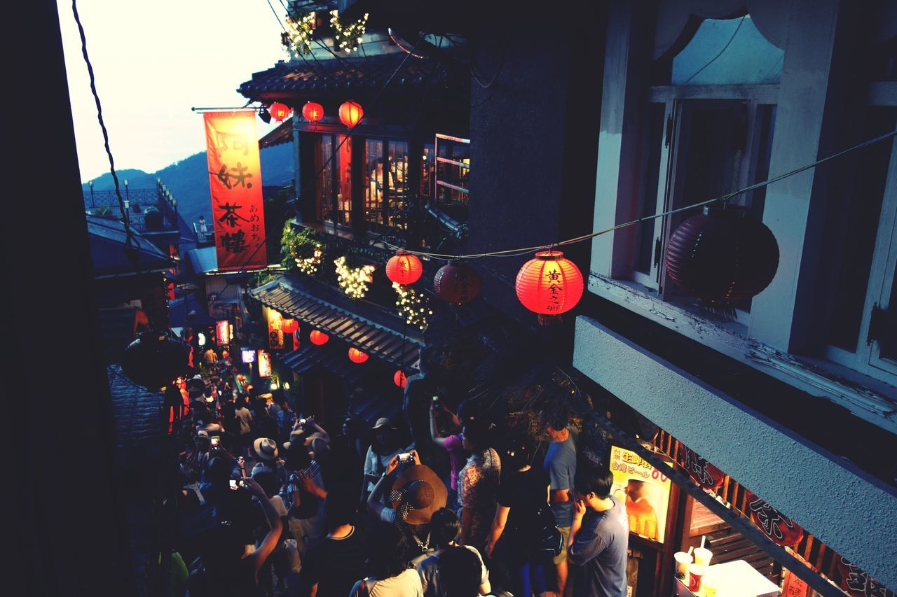 lantern, real people, large group of people, men, chinese lantern, illuminated, architecture, hanging, built structure, celebration, cultures, paper lantern, women, building exterior, outdoors, night, city, crowd, sky, people