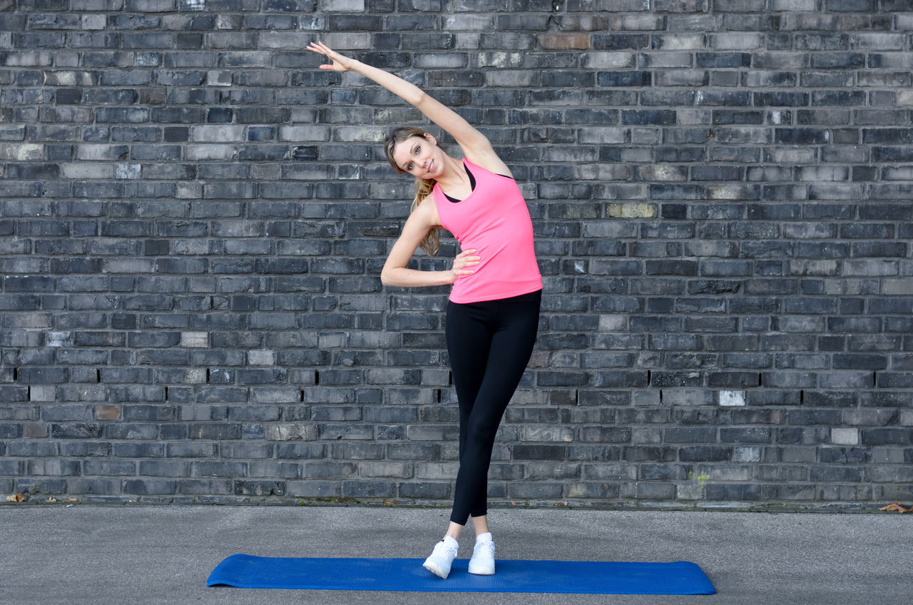 Adult Adults Only Day Exercise Equipment Exercising Flexibility Full Length Gym Healthy Lifestyle Leggings Lifestyles One Person One Woman Only Only Women Outdoors People Self Improvement Sport Sports Clothing Sports Training Standing Stretching Women