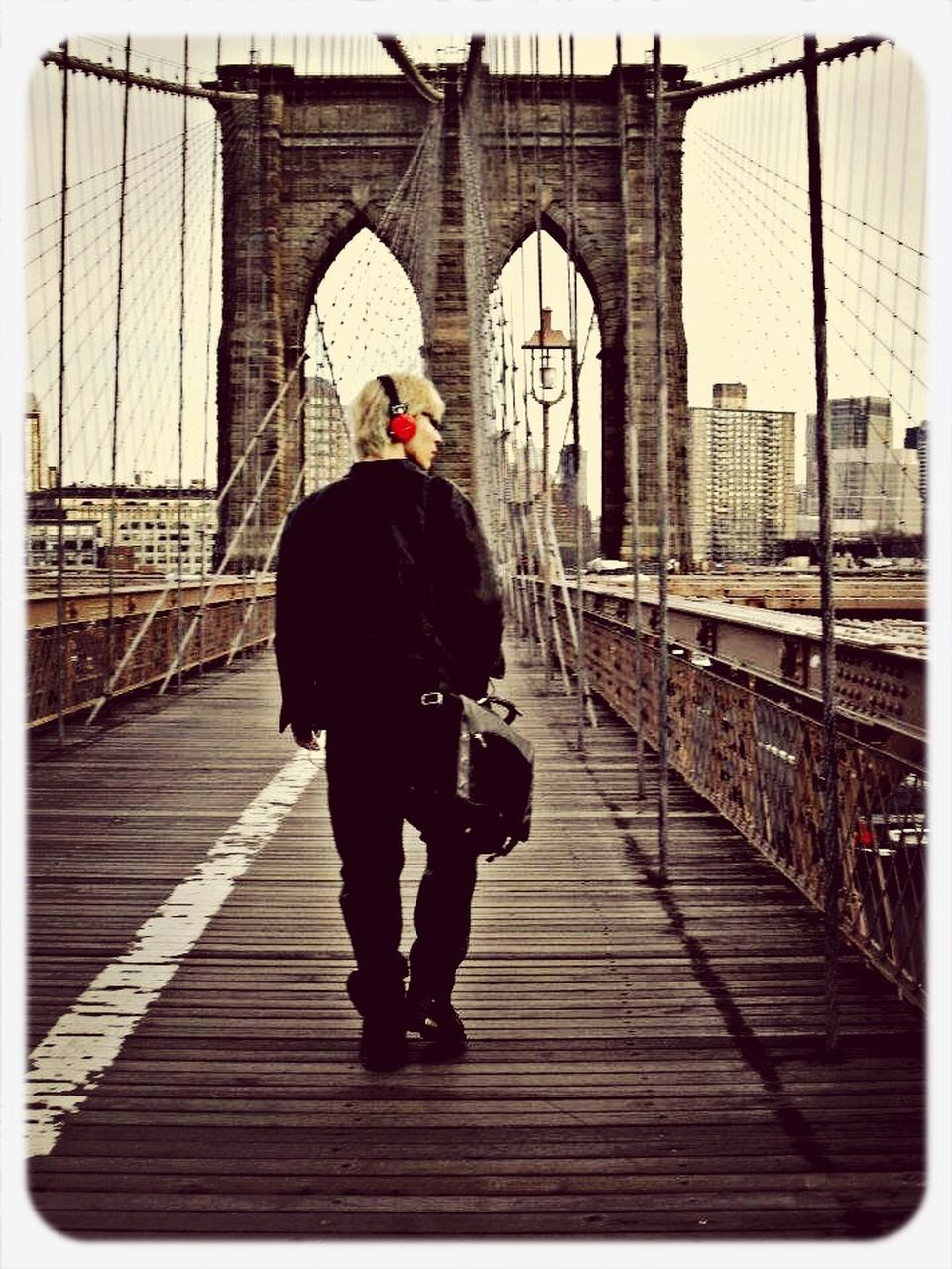 full length, bridge - man made structure, built structure, architecture, connection, railing, rear view, real people, walking, outdoors, footbridge, day, building exterior, transportation, bridge, togetherness, men, sky, adult, people