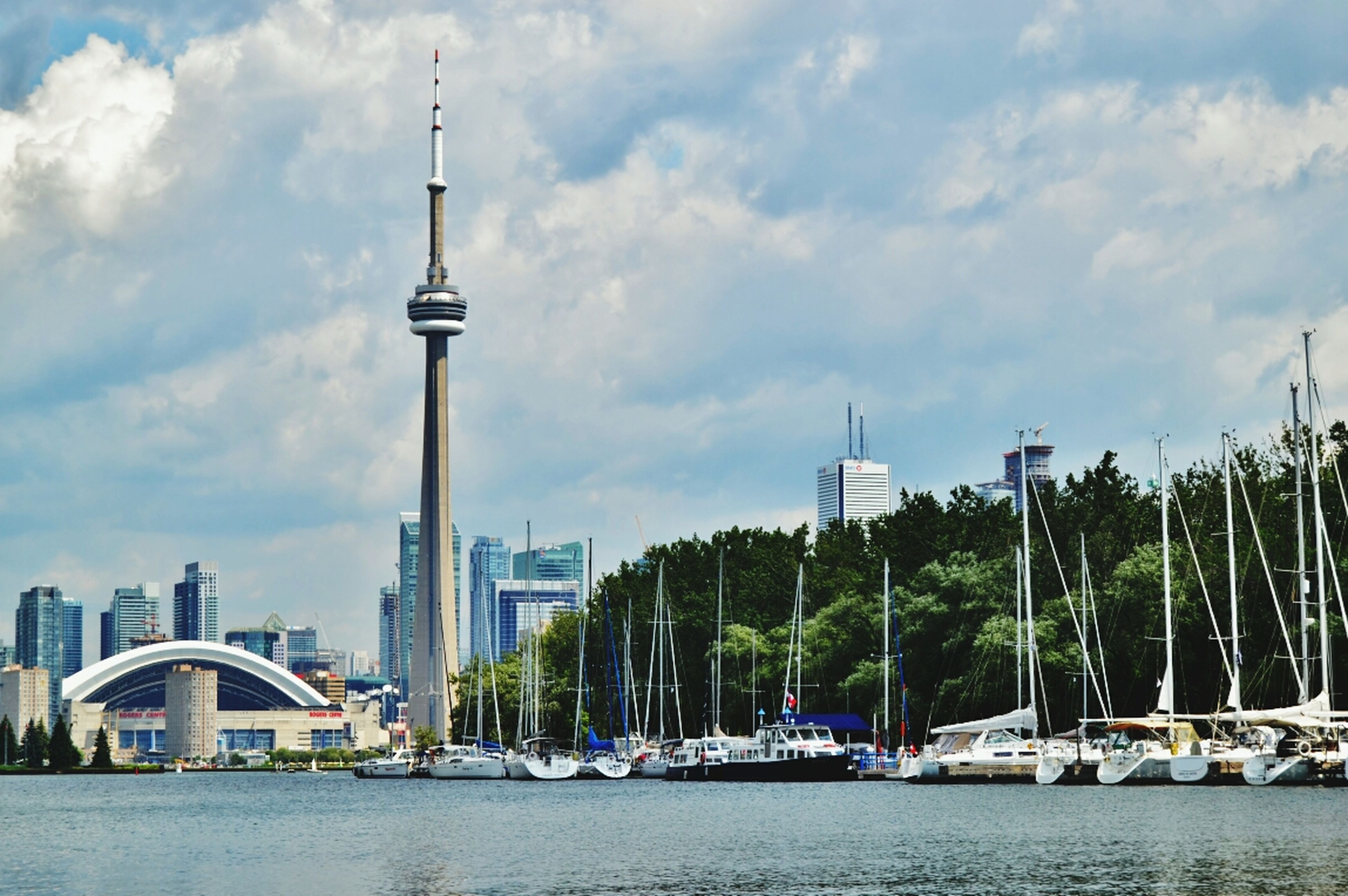 building exterior, architecture, built structure, sky, water, city, tower, waterfront, cloud - sky, tall - high, river, tree, cityscape, sea, cloud, nautical vessel, skyscraper, travel destinations, cloudy, day