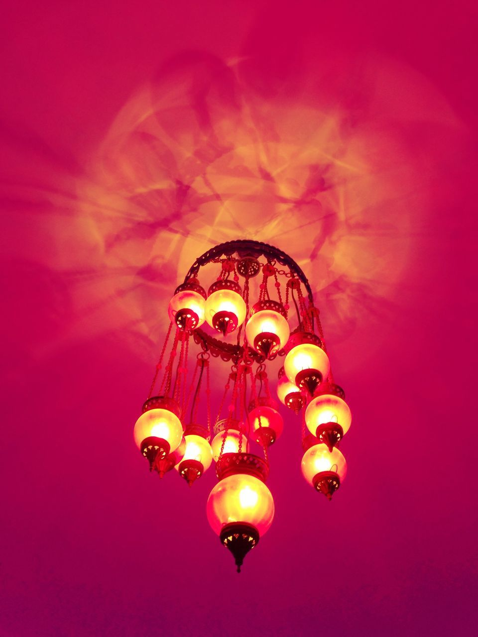 Low Angle View Of Illuminated Chandelier Hanging From Pink Ceiling