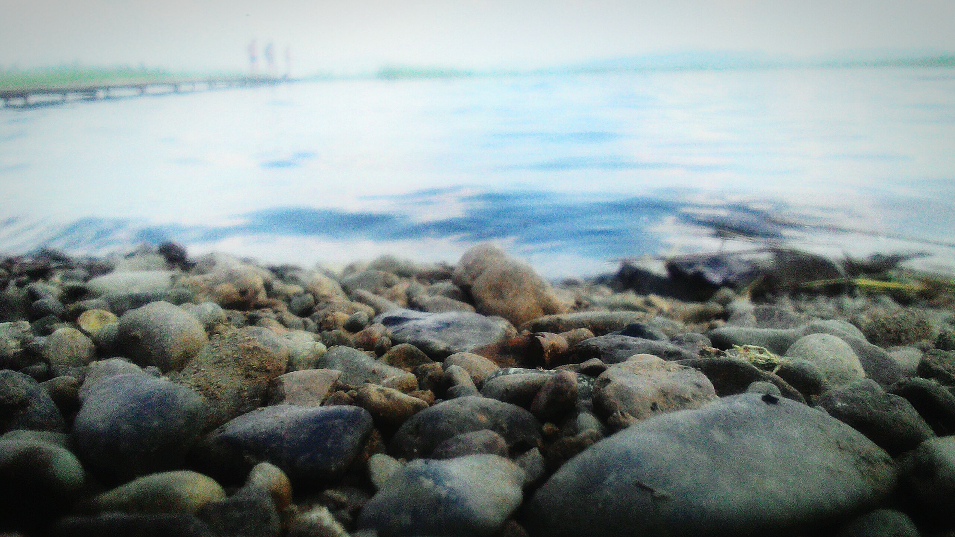 water, pebble, stone - object, shore, nature, rock - object, tranquility, surface level, beauty in nature, tranquil scene, stone, scenics, day, rock, outdoors, sky, no people, idyllic, selective focus, non-urban scene, abundance, remote, non urban scene, close-up, pebble beach