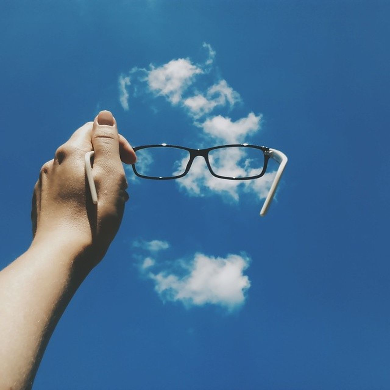 human hand, human body part, sky, blue, one person, eyeglasses, personal perspective, cloud - sky, real people, day, holding, low angle view, outdoors, men, eyesight, close-up, adult, people