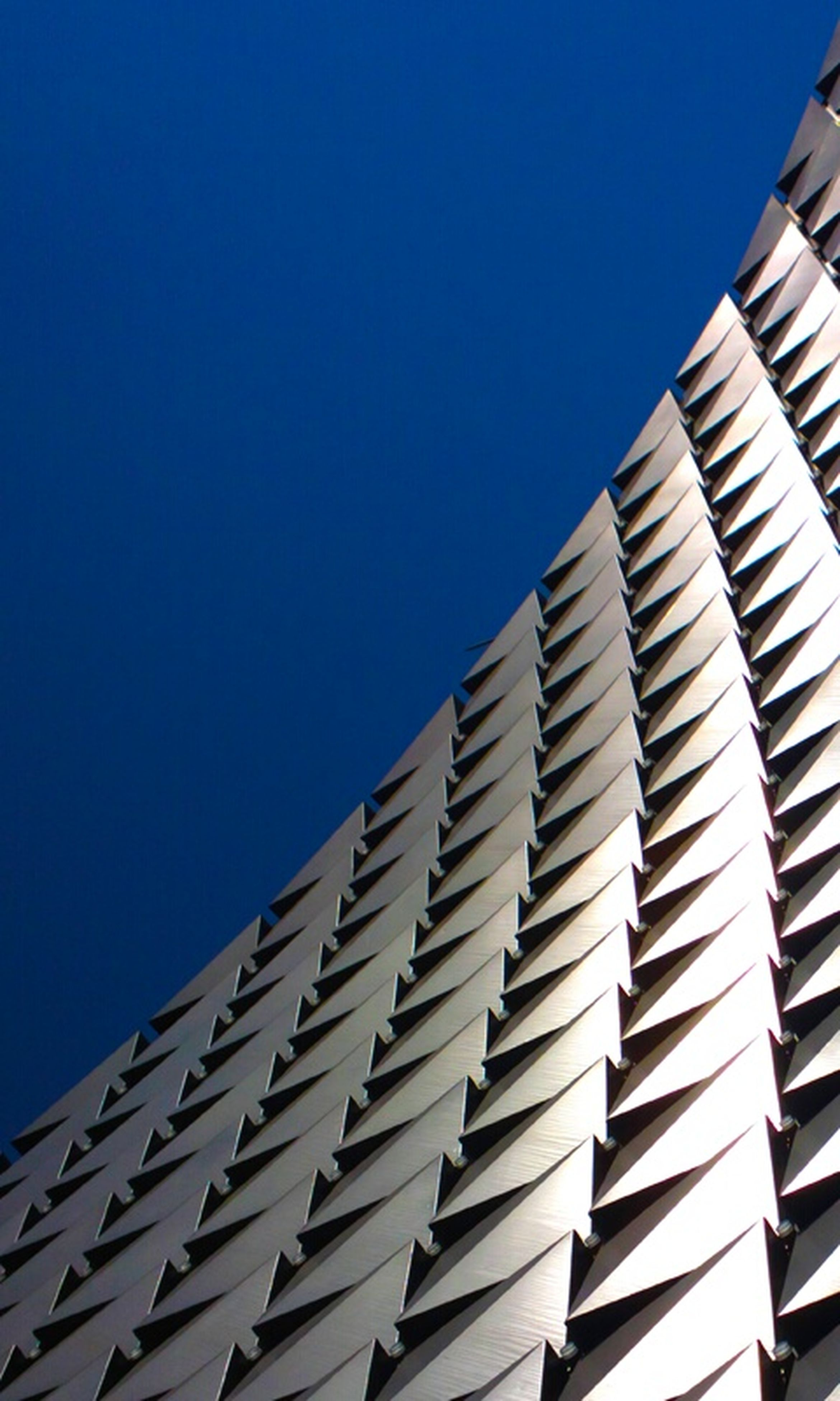 clear sky, low angle view, architecture, building exterior, built structure, blue, copy space, modern, building, city, high section, day, office building, outdoors, part of, no people, tall - high, sunlight, pattern, sky