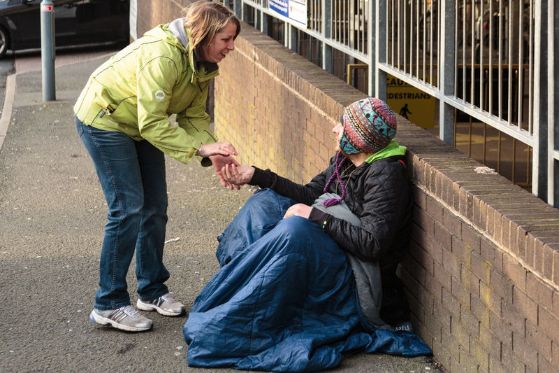 A beggar sitting outside the Rep car park in Birmingham city centre receiving money from a passing stranger in an act of generosity and kindness. Beggar Begging Birmingham UK Capture The Moment Coat Day Documentary Generosity Generosity And Warmth Giving Hat Homeless Homelessness  Horizontal Man Money Natural Light Outdoors Random Acts Of Kindness Sleeping Bag Social Issues Two People Unstaged Warm Clothing Woman