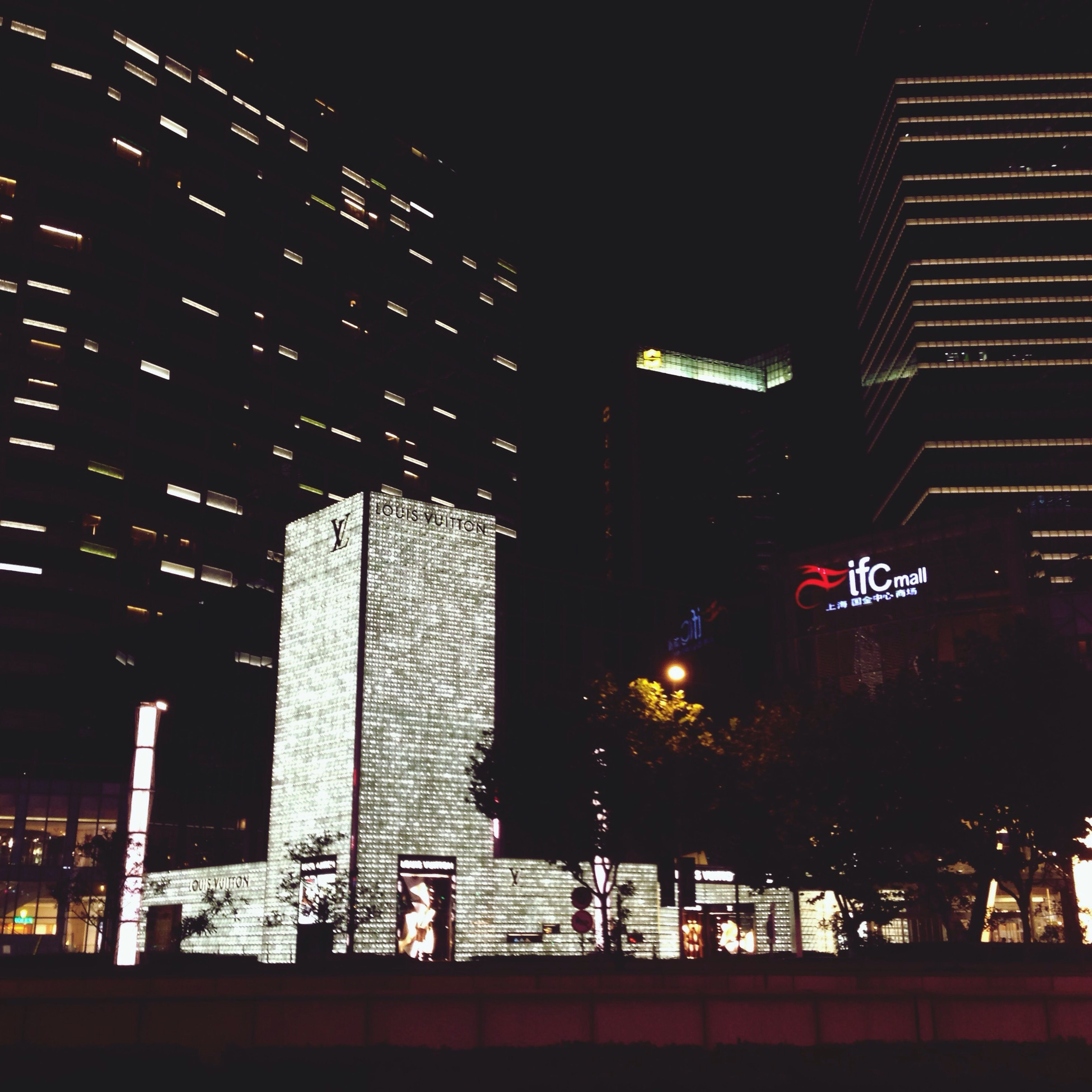 architecture, building exterior, built structure, illuminated, night, city, text, communication, western script, low angle view, building, modern, office building, sky, tower, outdoors, skyscraper, city life, no people, information sign