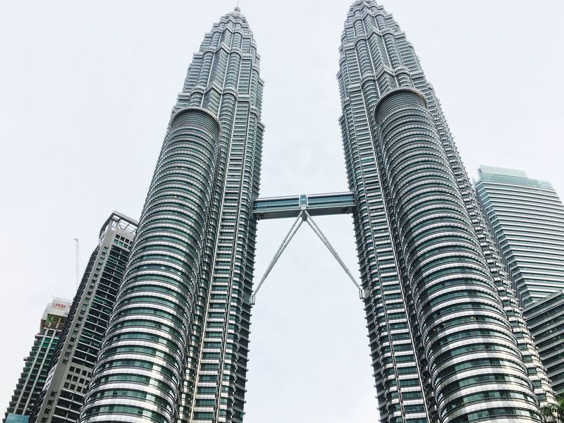 Architecture Built Structure Tall - High Skyscraper Low Angle View Building Exterior Modern Tower City Day Outdoors Travel Destinations No People Tall Clear Sky Sky Financial District  Architecturephotography The Architect - 2017 EyeEm Awards IPhoneography Panorama Petronas Twin Towers Kuala Lumpur Malaysia  Lovetotravel Vacations