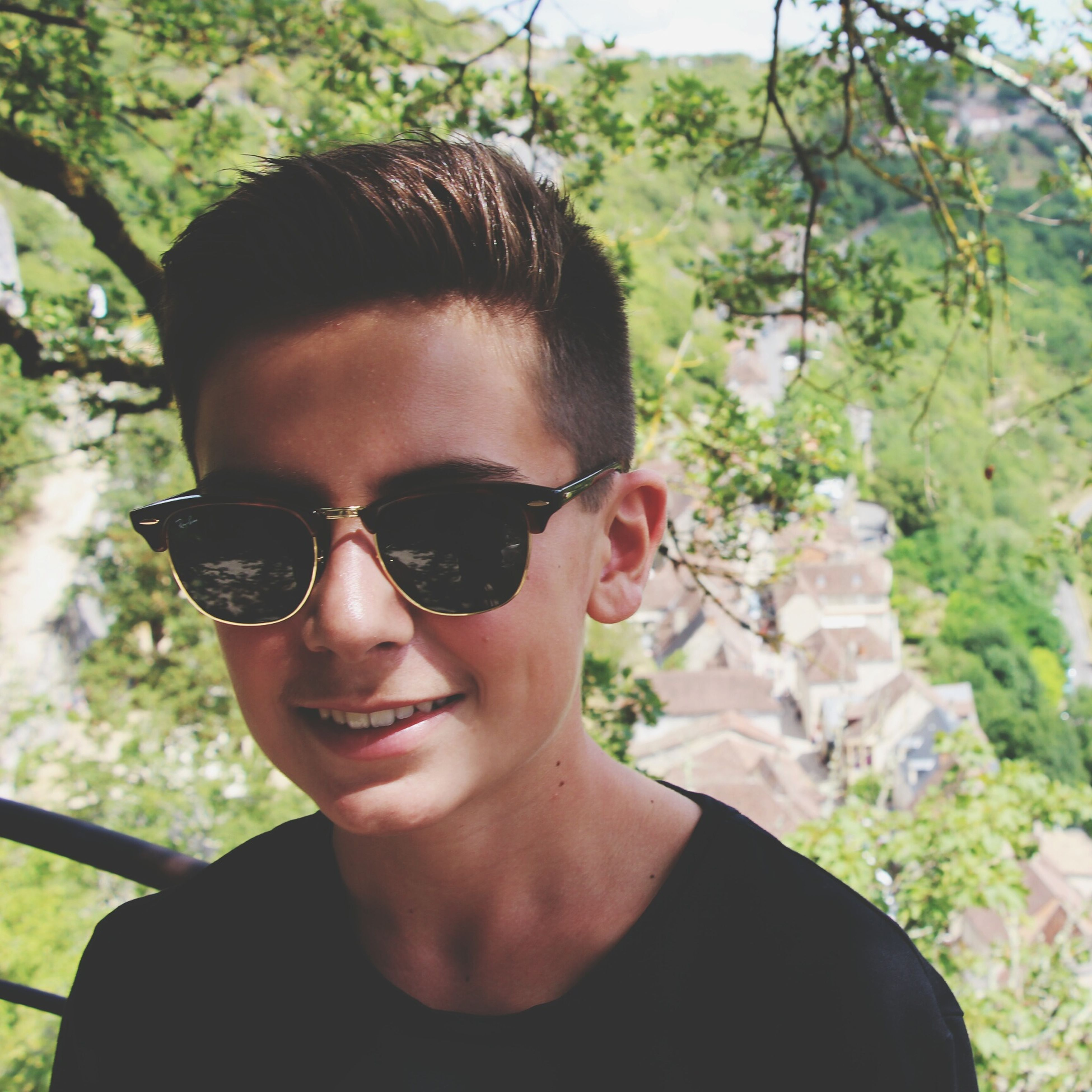 sunglasses, young adult, focus on foreground, headshot, close-up, front view, leisure activity, lifestyles, young men, person, looking at camera, green color, nature, handsome, summer, growth, freshness, outdoors, day