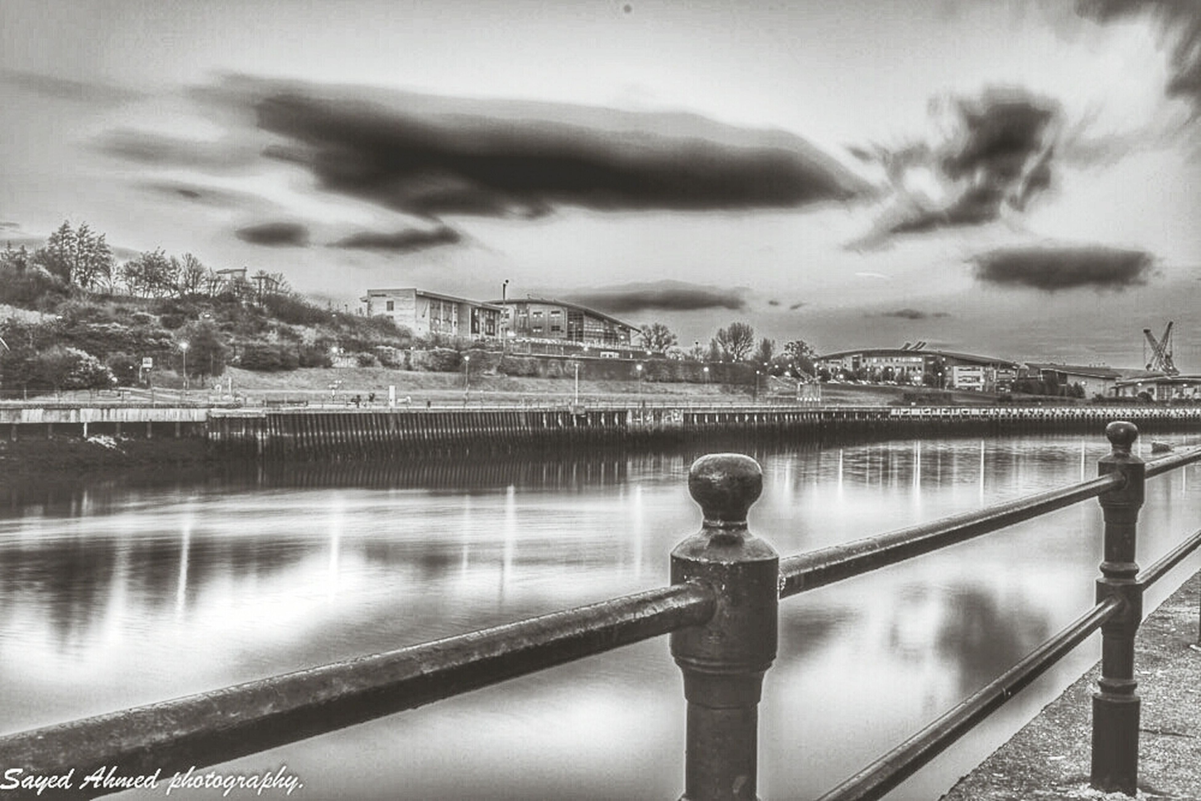 railing, water, sky, architecture, built structure, bridge - man made structure, river, building exterior, connection, cloud - sky, city, metal, one person, cityscape, outdoors, dusk, bridge, day, weather, standing