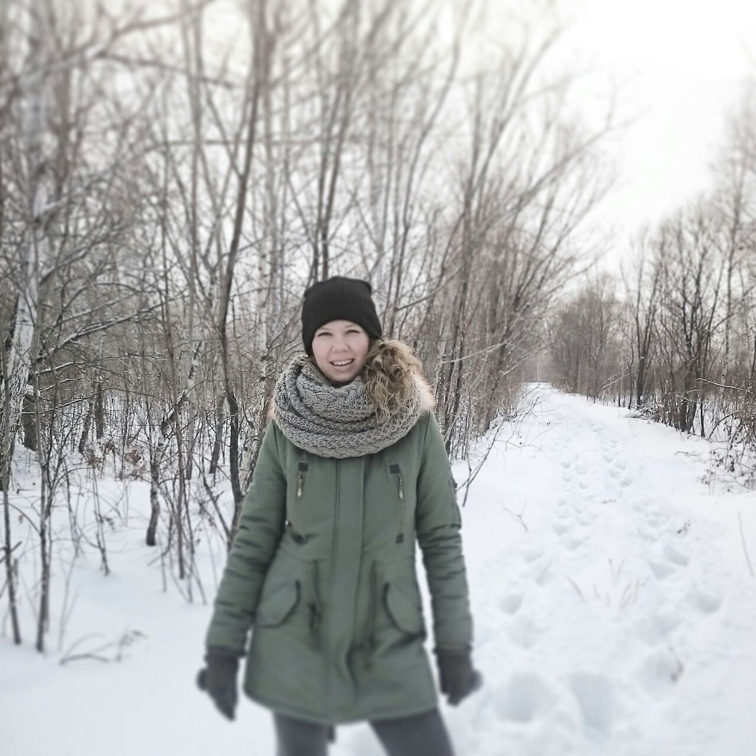 winter, snow, cold temperature, season, warm clothing, lifestyles, weather, leisure activity, tree, looking at camera, front view, person, portrait, standing, covering, bare tree, casual clothing, white color