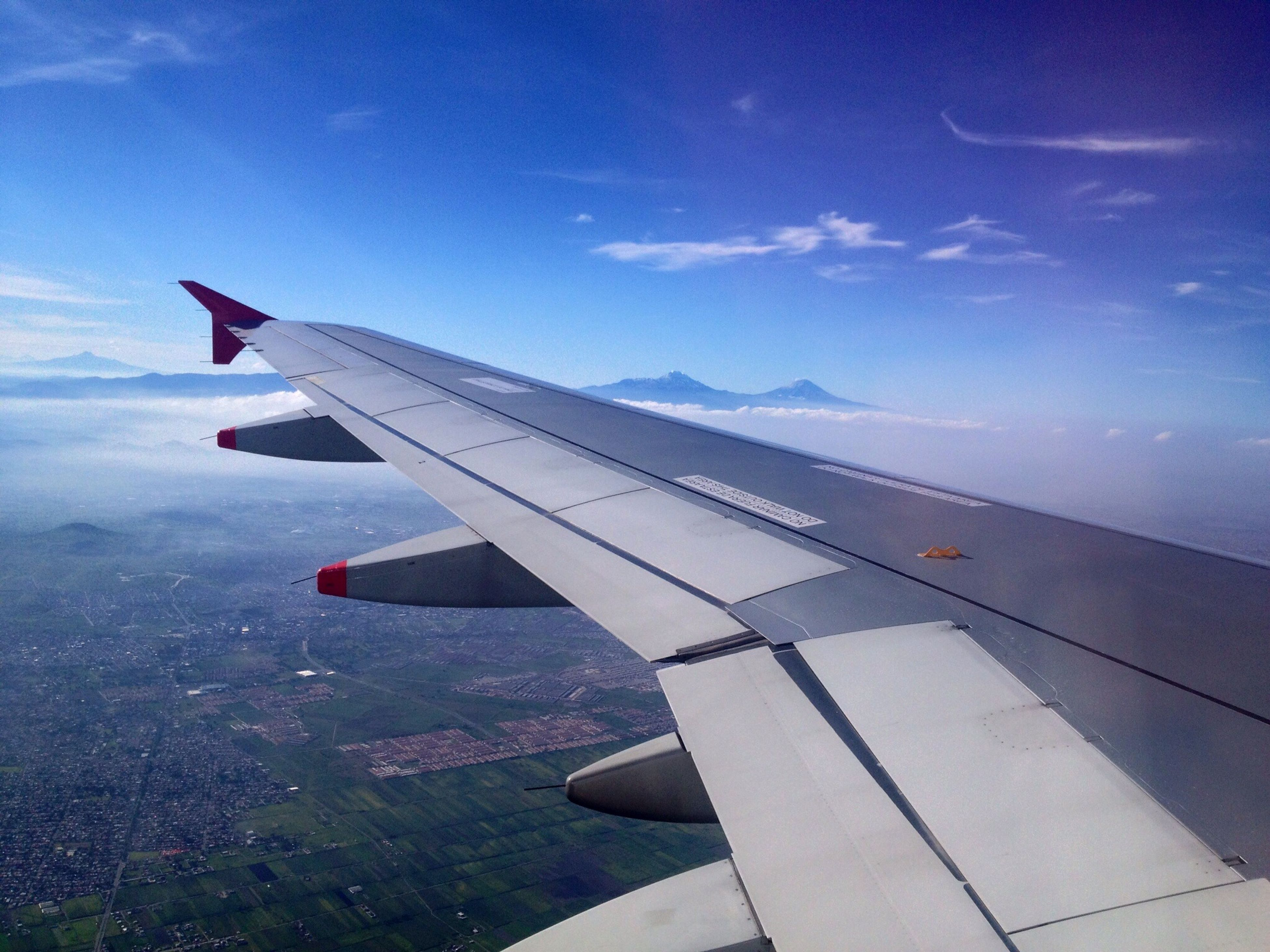 transportation, airplane, aircraft wing, mode of transport, air vehicle, flying, sky, part of, travel, cropped, cloud - sky, on the move, mid-air, journey, sea, aerial view, blue, nature, public transportation, cloud