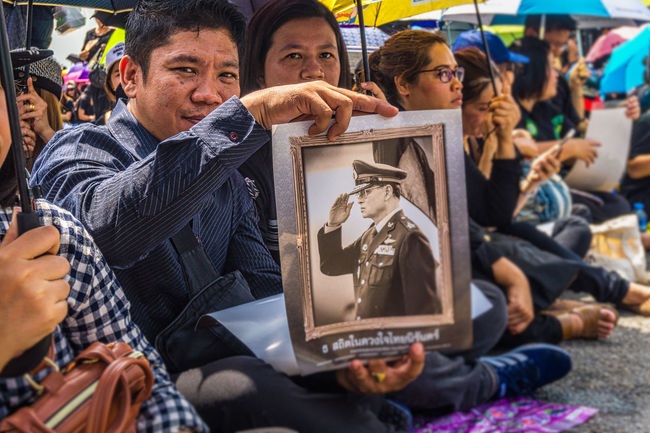 A young man holds up a picture of HM King Bhumipol Adulyadej on the day Thais came to Bangkok to sing the Royal Anthem in honour of their king. Adult Bangkok Day Horizontal King Bhumipol Adulyadet Lifestyles People Person Thailand Togetherness Travel Young Adult Young Women
