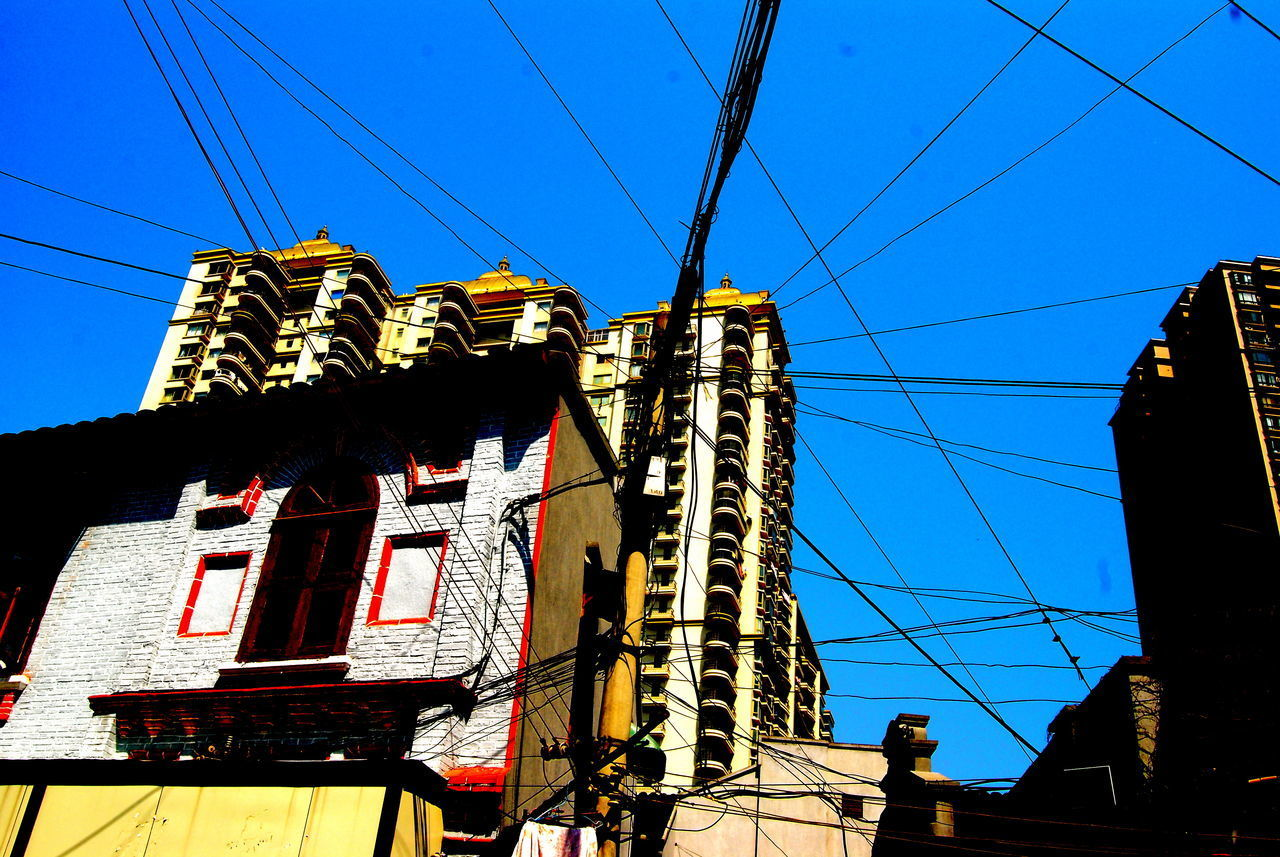 cable, low angle view, building exterior, architecture, built structure, power line, outdoors, day, blue, clear sky, sunlight, sky, no people, electricity pylon, technology