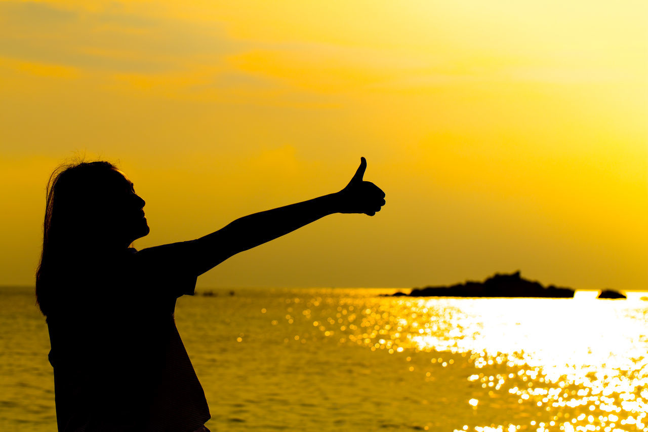 sunset, silhouette, sea, water, beauty in nature, one person, horizon over water, nature, real people, scenics, sky, standing, sun, outdoors, side view, lifestyles, women, yellow, young women, human hand, young adult, day, people