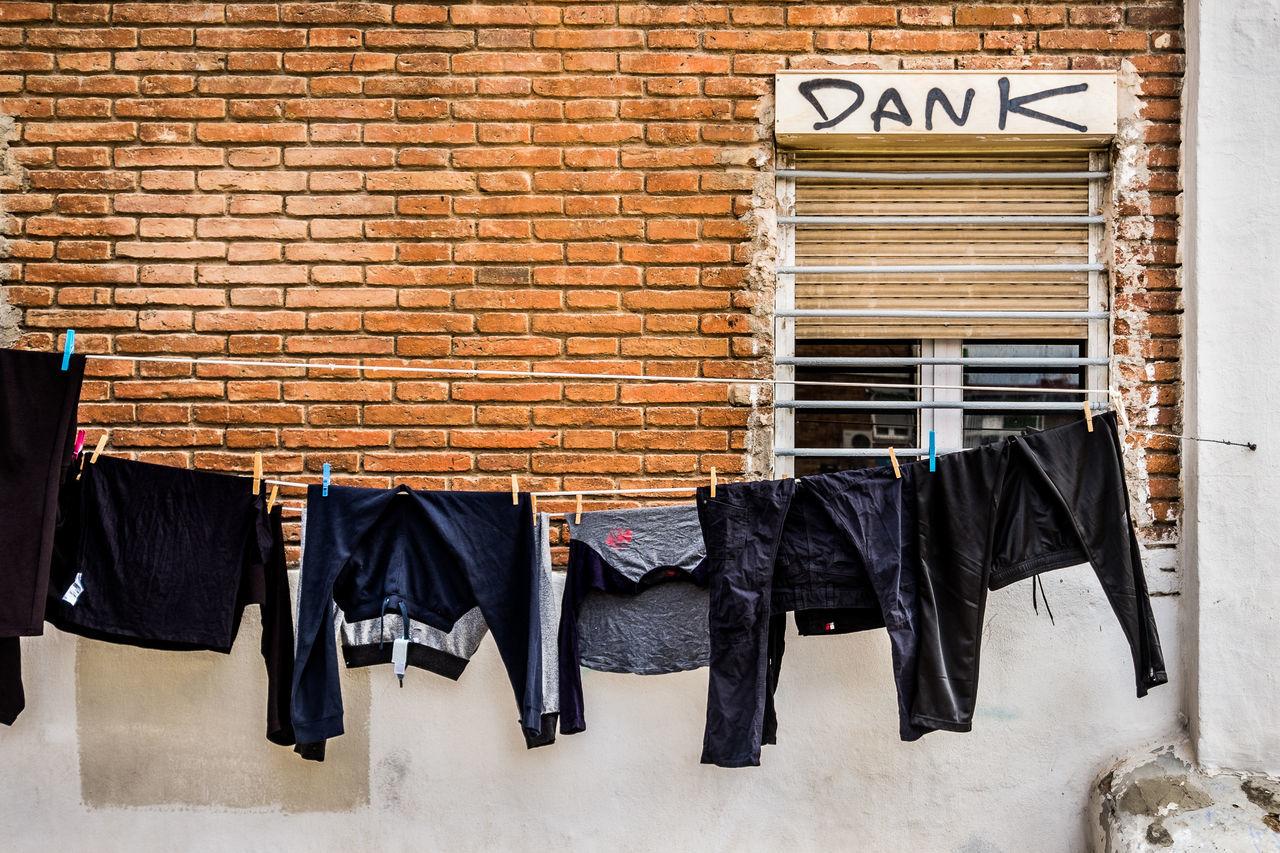 Hanging Brick Wall Clothing Coathanger Building Exterior No People Outdoors Graffiti