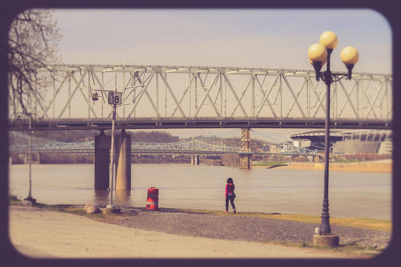 Bridge Bridge Over Water Bridges Cincinnati, Ohio Lamp Post Lamppost Leisure Activity Light Pole Lightpole Lightpost Ohio River One Person One Woman Person Rear View River Scenics Walking Walking By The River Woman