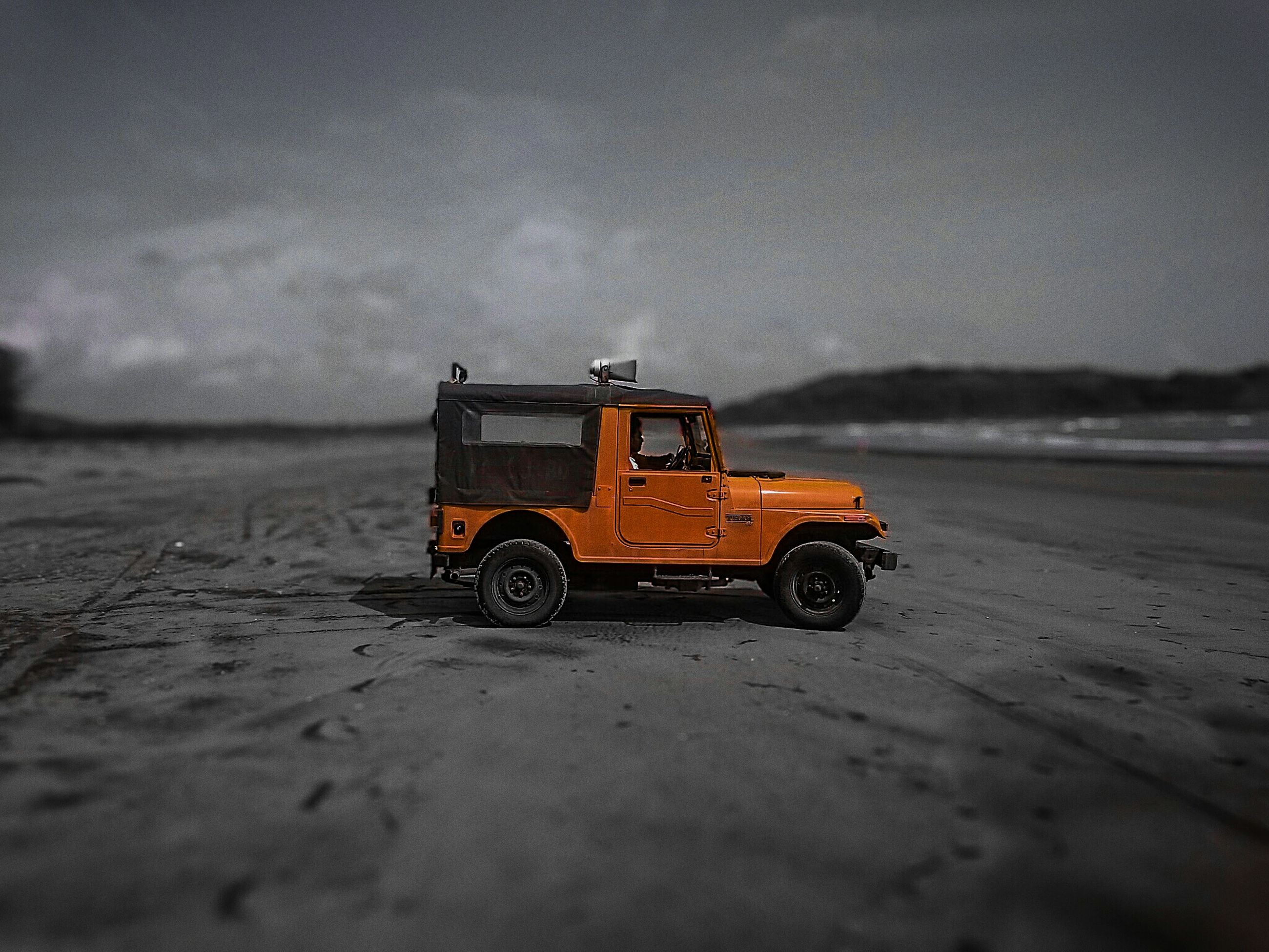 transportation, land vehicle, mode of transport, car, sky, street, sand, stationary, travel, outdoors, road, on the move, sunset, beach, building exterior, cloud - sky, no people, vehicle, selective focus, built structure