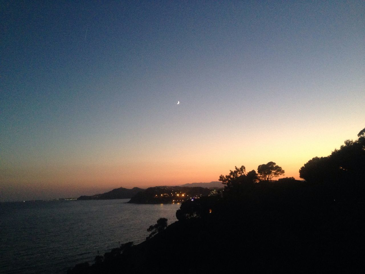moon, sunset, silhouette, scenics, nature, beauty in nature, tranquil scene, sky, tranquility, idyllic, clear sky, dusk, outdoors, night, crescent, no people, water, sea, half moon, astronomy, tree