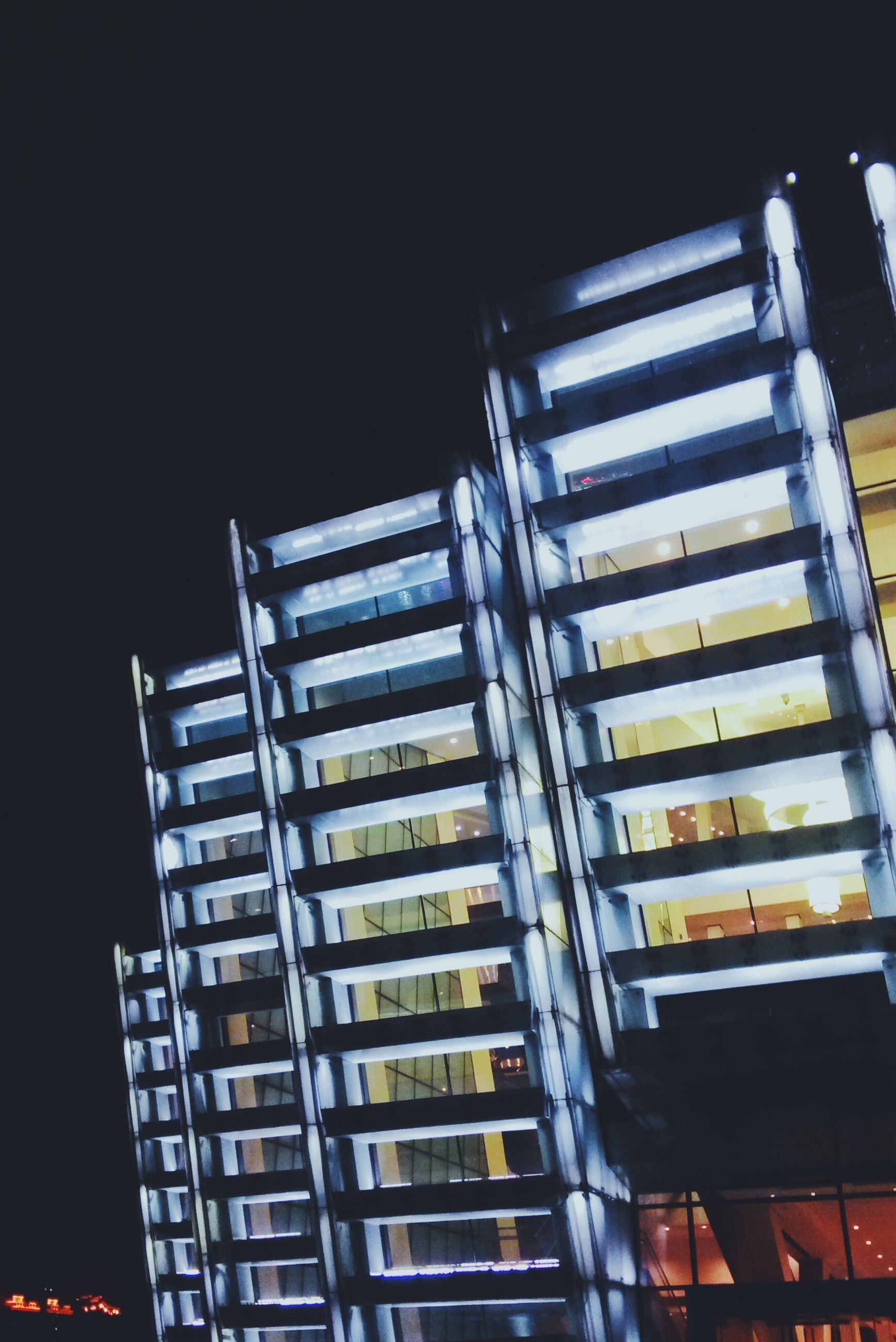architecture, low angle view, building exterior, built structure, night, illuminated, building, window, city, no people, residential building, residential structure, modern, outdoors, pattern, sky, glass - material, clear sky, lighting equipment, office building