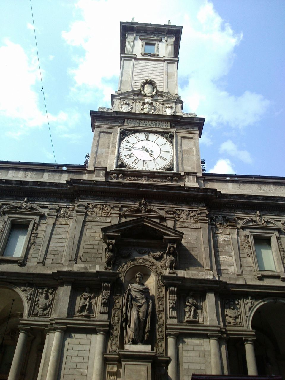low angle view, human representation, sky, architecture, building exterior, cloud - sky, statue, built structure, sculpture, male likeness, clock, clock tower, time, travel destinations, day, outdoors, history, no people, clock face, city, roman numeral