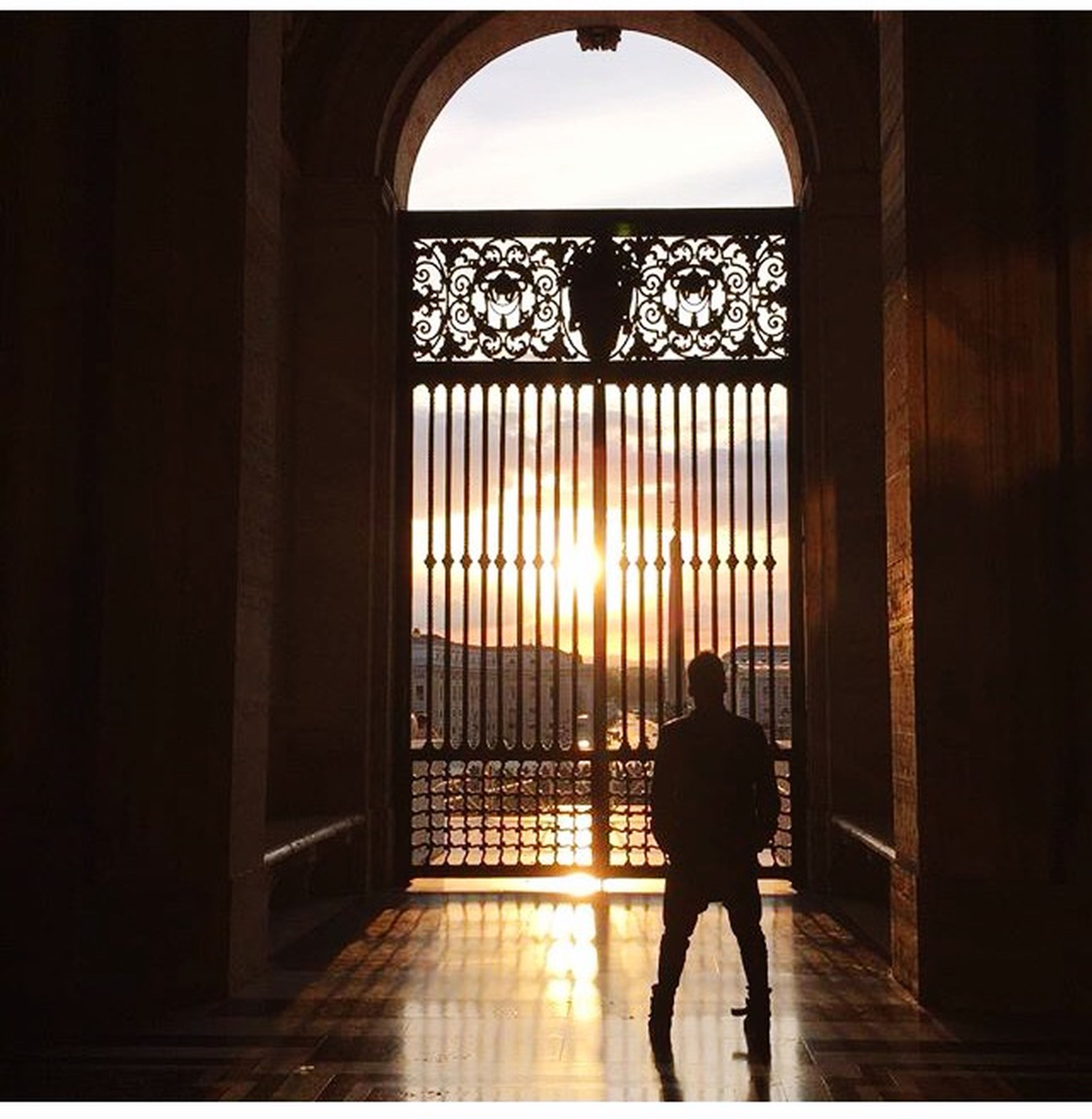indoors, silhouette, full length, lifestyles, arch, architecture, built structure, men, rear view, walking, leisure activity, standing, person, sunlight, corridor, window, archway