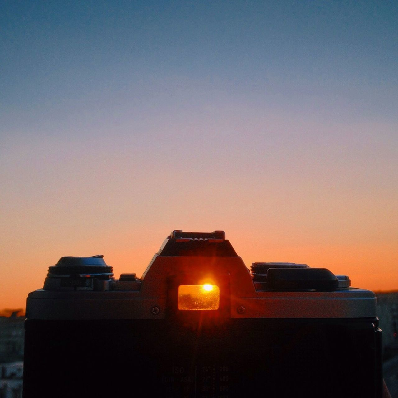sunset, orange color, no people, clear sky, illuminated, camera - photographic equipment, outdoors, architecture, sky, built structure, building exterior, technology, photography themes, close-up, digital single-lens reflex camera, day
