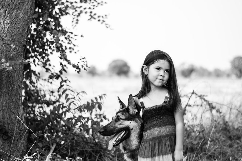 Alsatian Black And White Childhood Clear Sky Daughter Day Field Front View German Shepherd Happiness I Love My Dog Leisure Activity Lifestyles Nature Outdoors Person Pet Portrait Sky Tree Young Adult