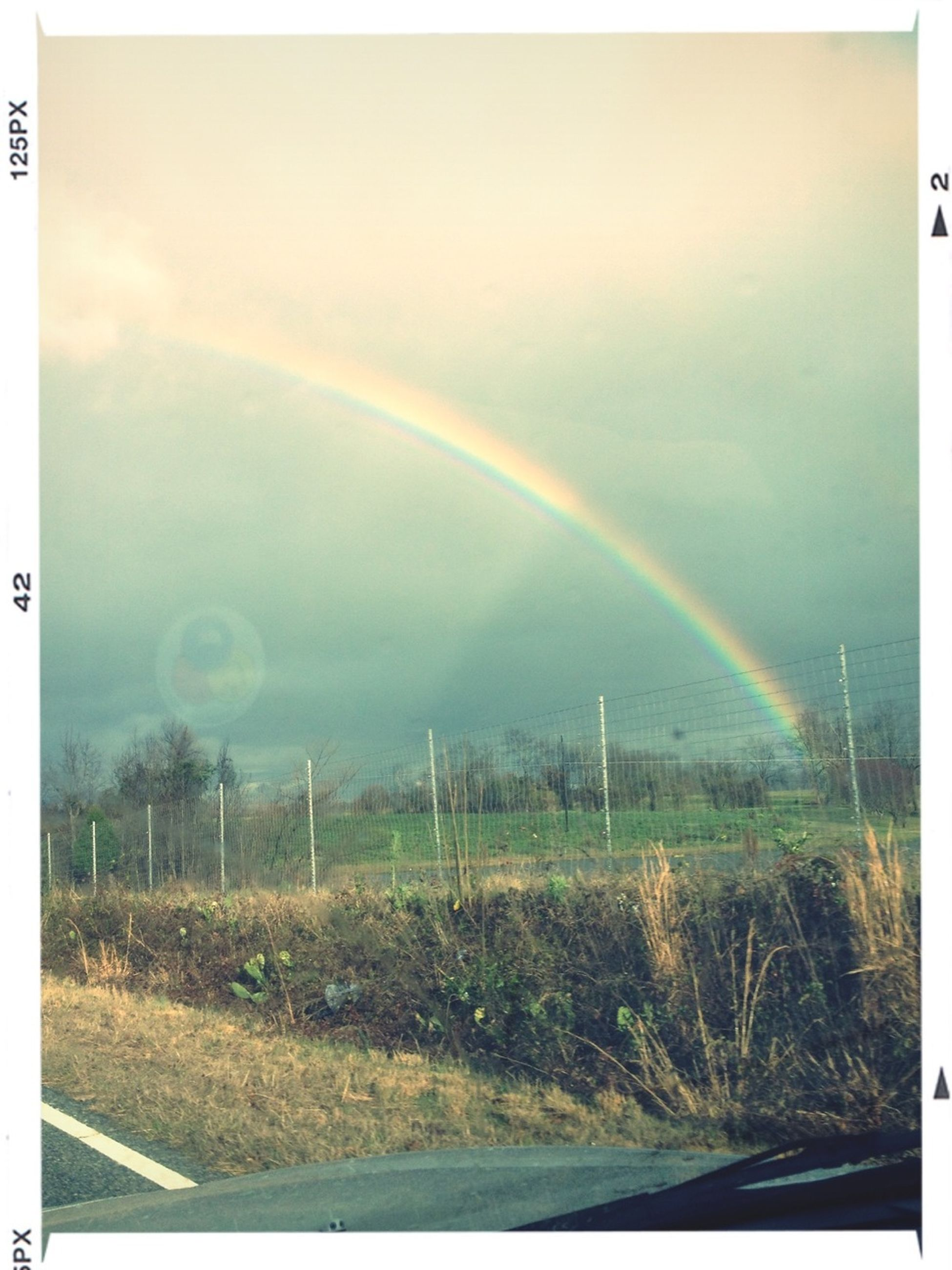 transfer print, rainbow, landscape, auto post production filter, sky, field, scenics, tranquility, tranquil scene, grass, beauty in nature, road, nature, weather, idyllic, green color, outdoors, cloud - sky, no people, grassy