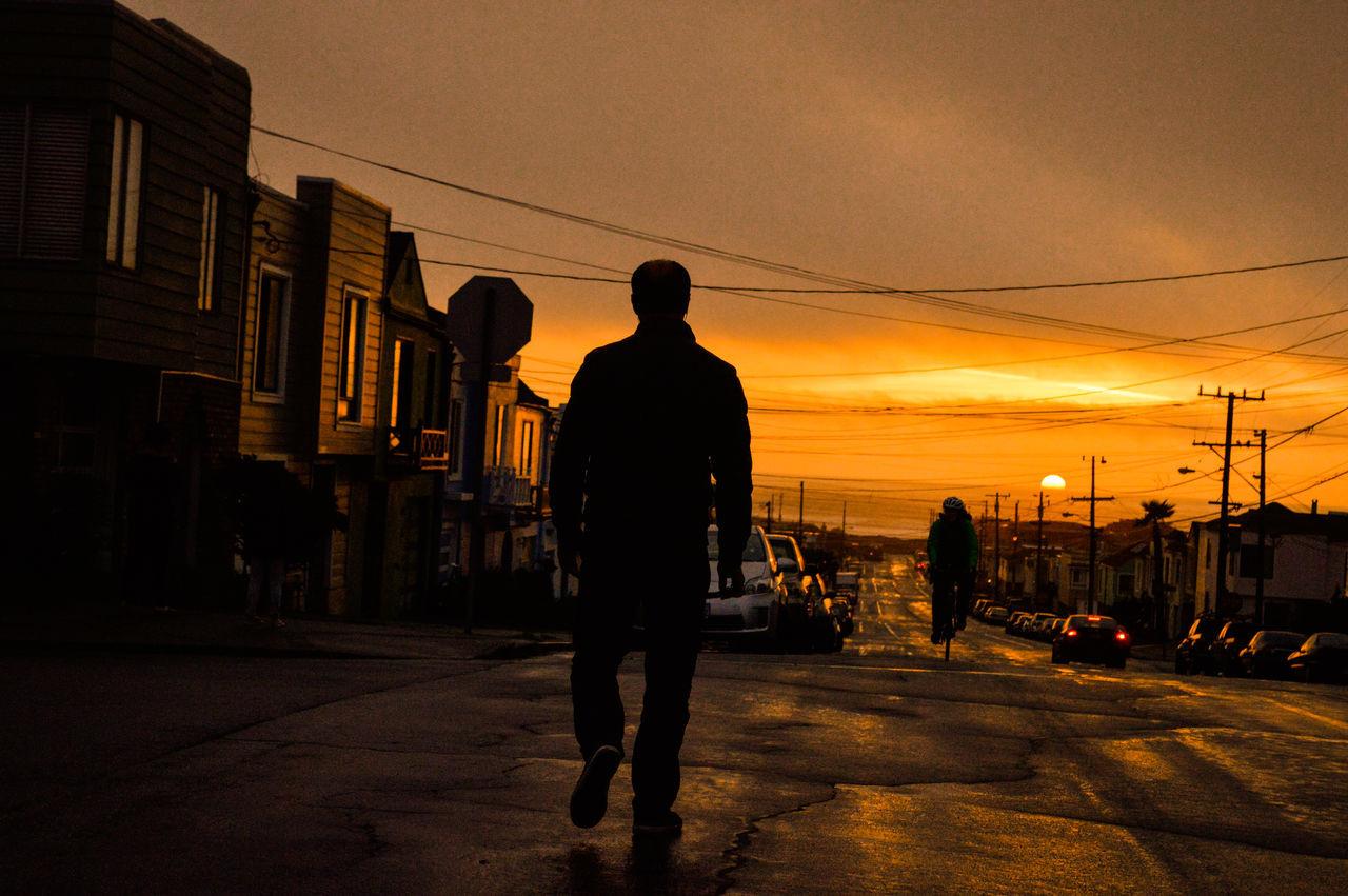 Full Length Rear View Of Silhouette Man Walking On Street Against Sky During Sunset