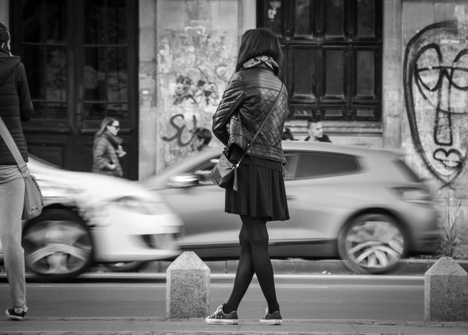 Cross-shaped legs at the bus stop Black And White Casual Clothing City Street Dramatic Angles Girl Girl Waiting Legs Lifestyles Monochrome Photography Motion Real People Standing Street Street Photography Young Adult Embrace Urban Life Women Around The World