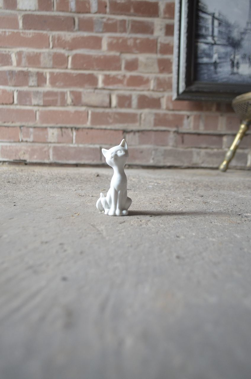 Close-Up Of Cat Figurine On Floor Against Brick Wall