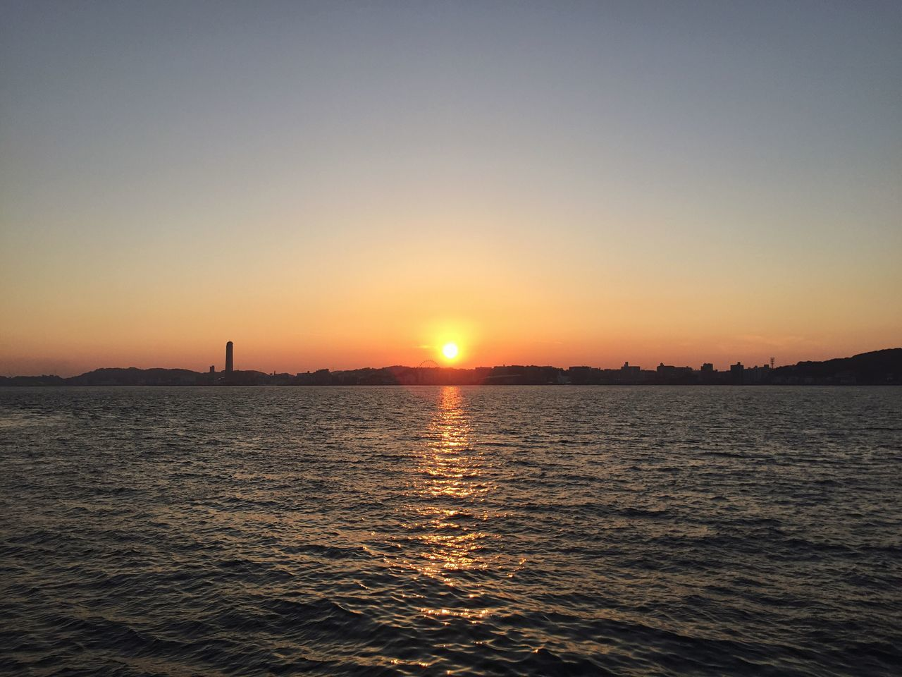 Sunset across the straits. Moji Japan KYUSHU Sunset Sun Beauty In Nature Scenics Orange Color Nature Sea Tranquil Scene Tranquility Silhouette Idyllic Water Sky No People Outdoors Sunlight Waterfront Clear Sky