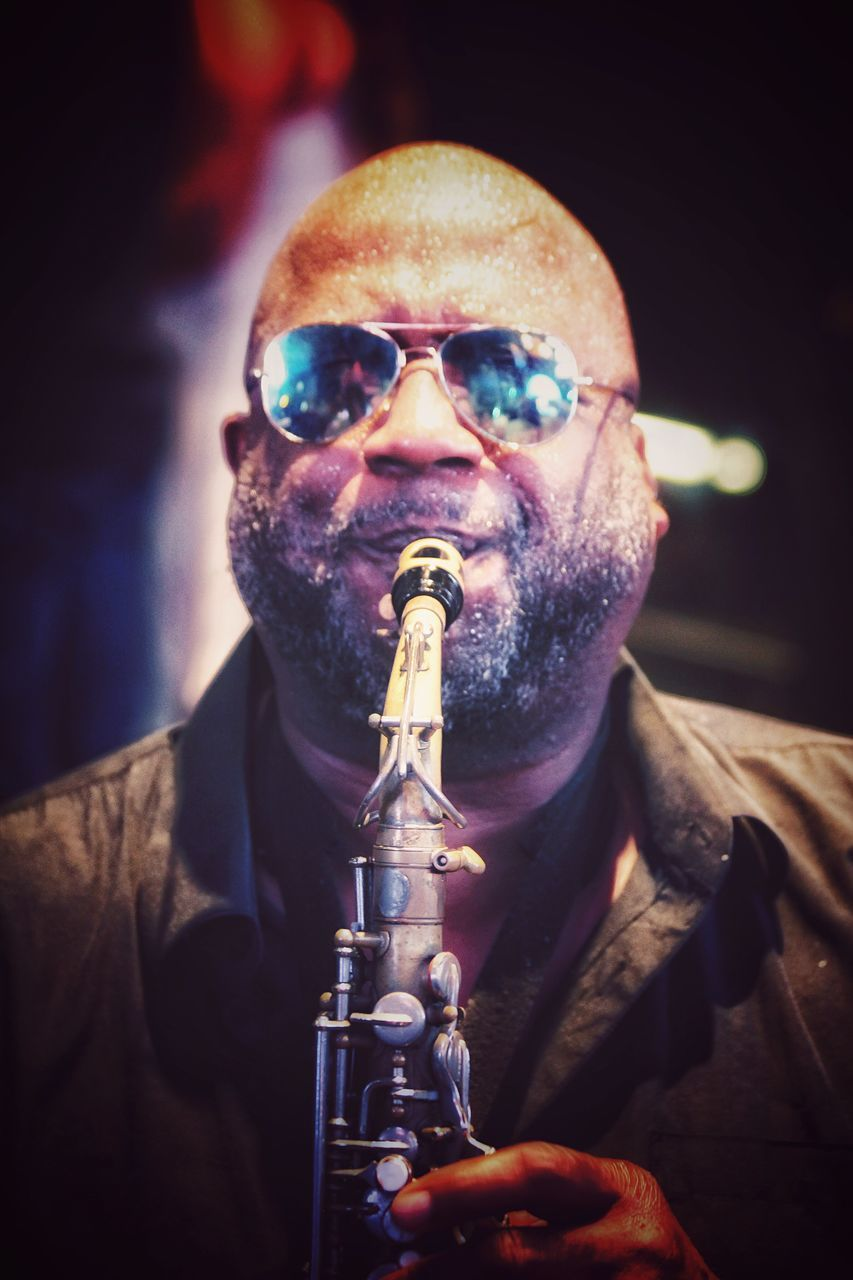 sunglasses, front view, mature men, portrait, one person, real people, looking at camera, beard, leisure activity, mature adult, lifestyles, night, musical instrument, outdoors, musician