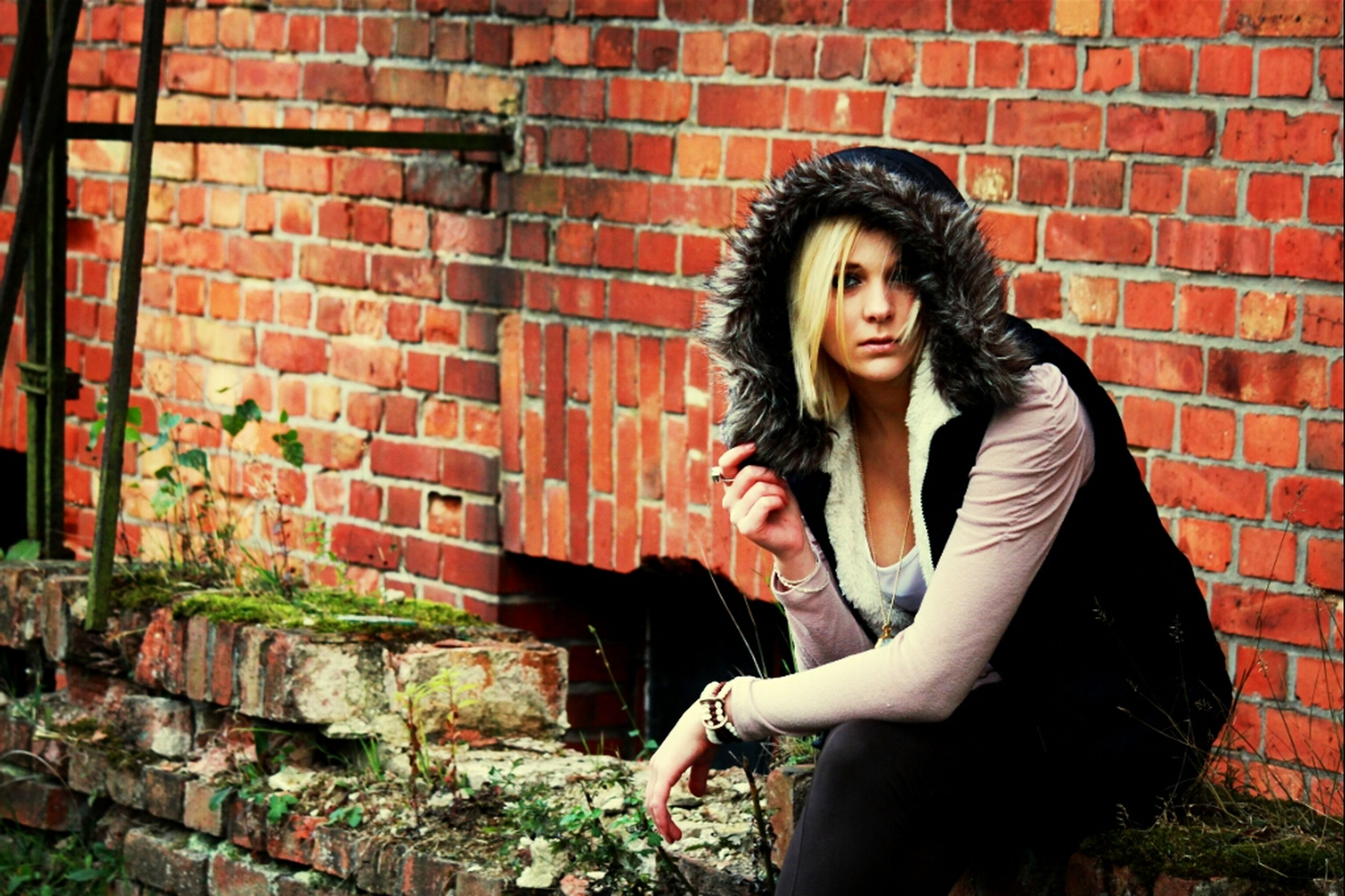young adult, young women, brick wall, looking at camera, portrait, person, lifestyles, front view, casual clothing, standing, wall - building feature, long hair, leisure activity, smiling, architecture, built structure, three quarter length
