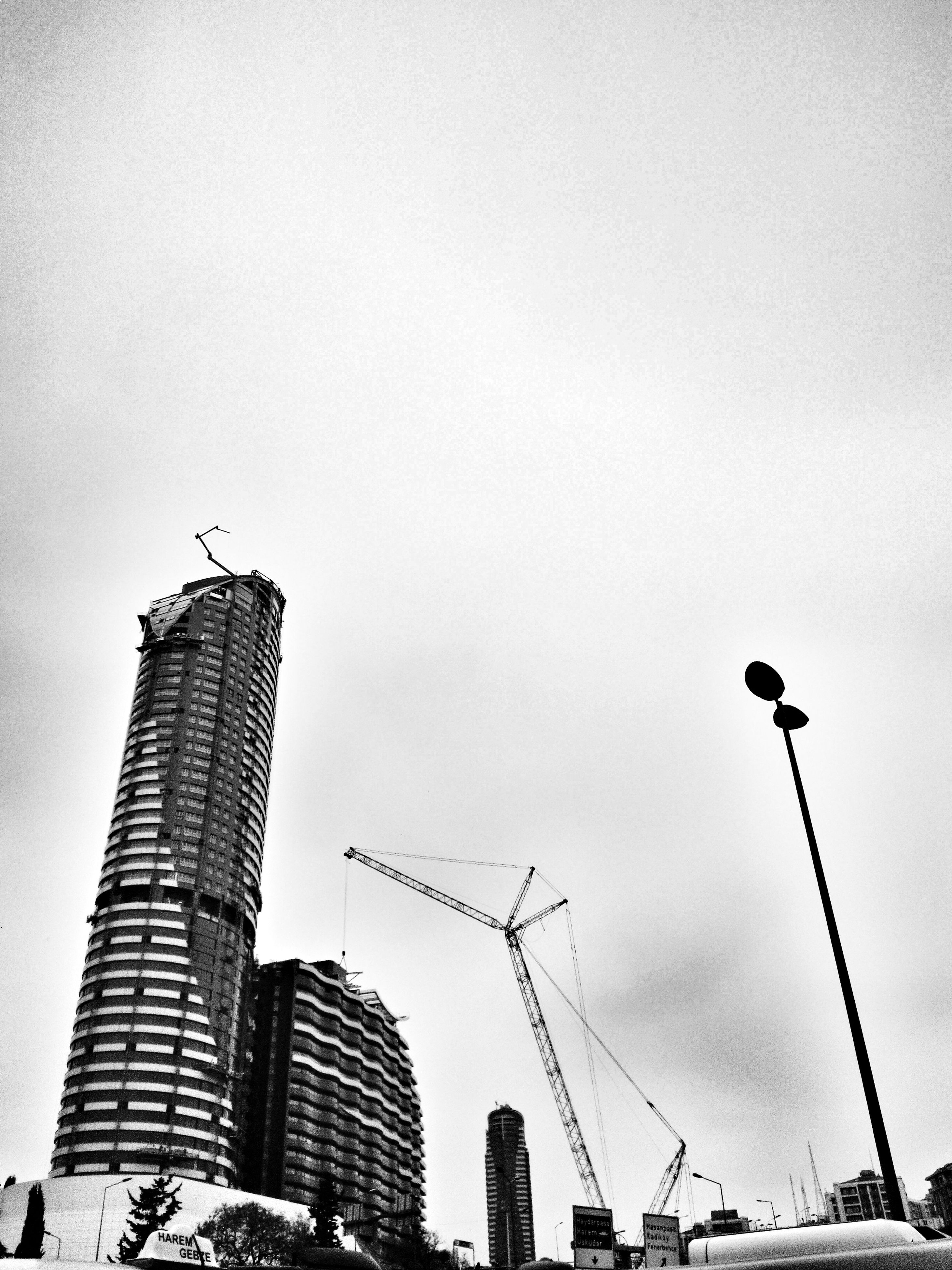 low angle view, architecture, crane - construction machinery, building exterior, built structure, tall - high, construction site, silhouette, development, clear sky, tower, sky, crane, copy space, city, skyscraper, construction, bird, animals in the wild, incomplete