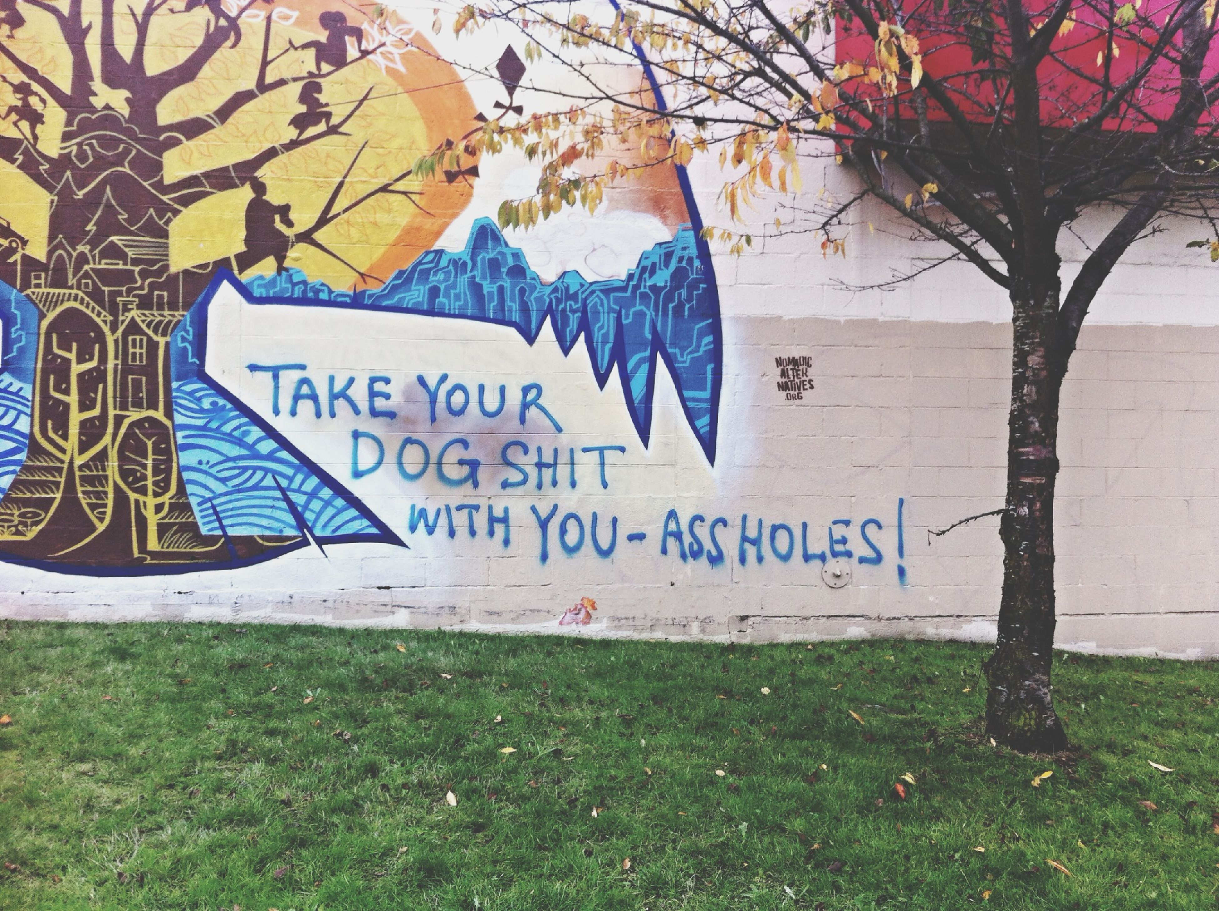text, graffiti, art, creativity, western script, art and craft, communication, tree, grass, day, human representation, bare tree, wall - building feature, built structure, outdoors, animal representation, park - man made space, street art, capital letter, no people