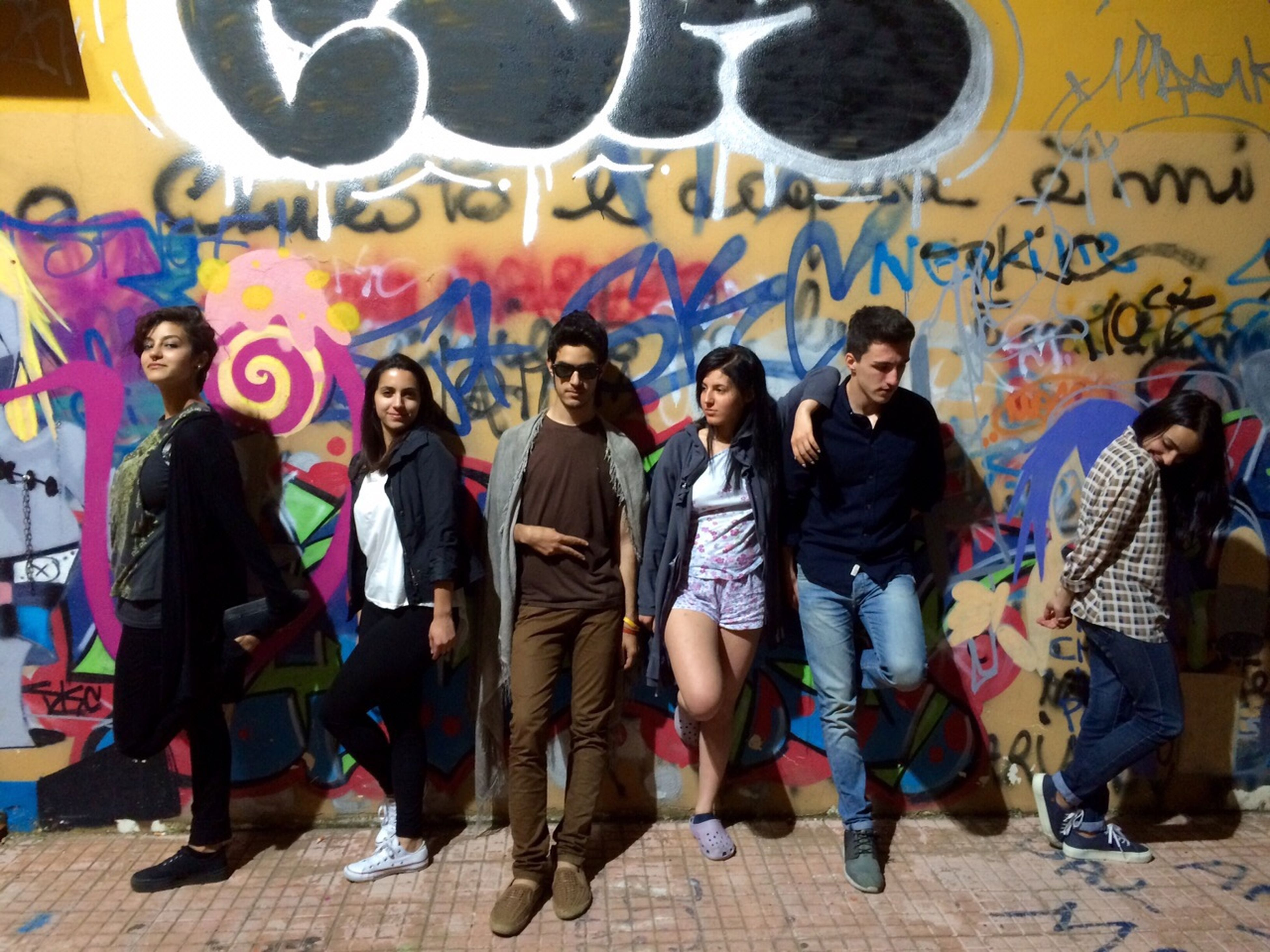 lifestyles, leisure activity, text, men, large group of people, togetherness, casual clothing, western script, person, full length, communication, wall - building feature, happiness, friendship, standing, graffiti, fun, love, young men