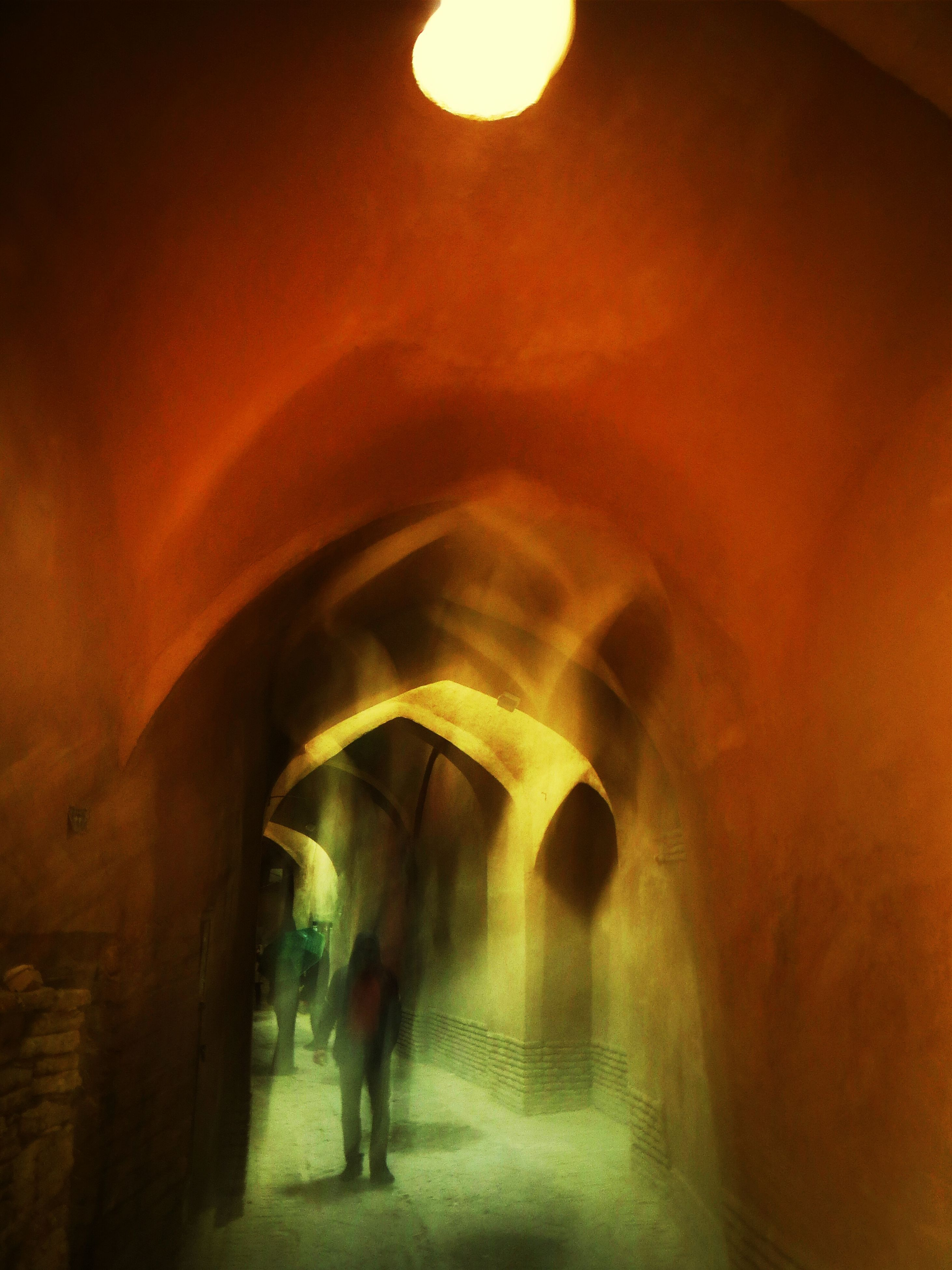 illuminated, indoors, architecture, arch, tunnel, built structure, lifestyles, lighting equipment, men, night, the way forward, walking, leisure activity, person, ceiling, light - natural phenomenon, wall - building feature, unrecognizable person